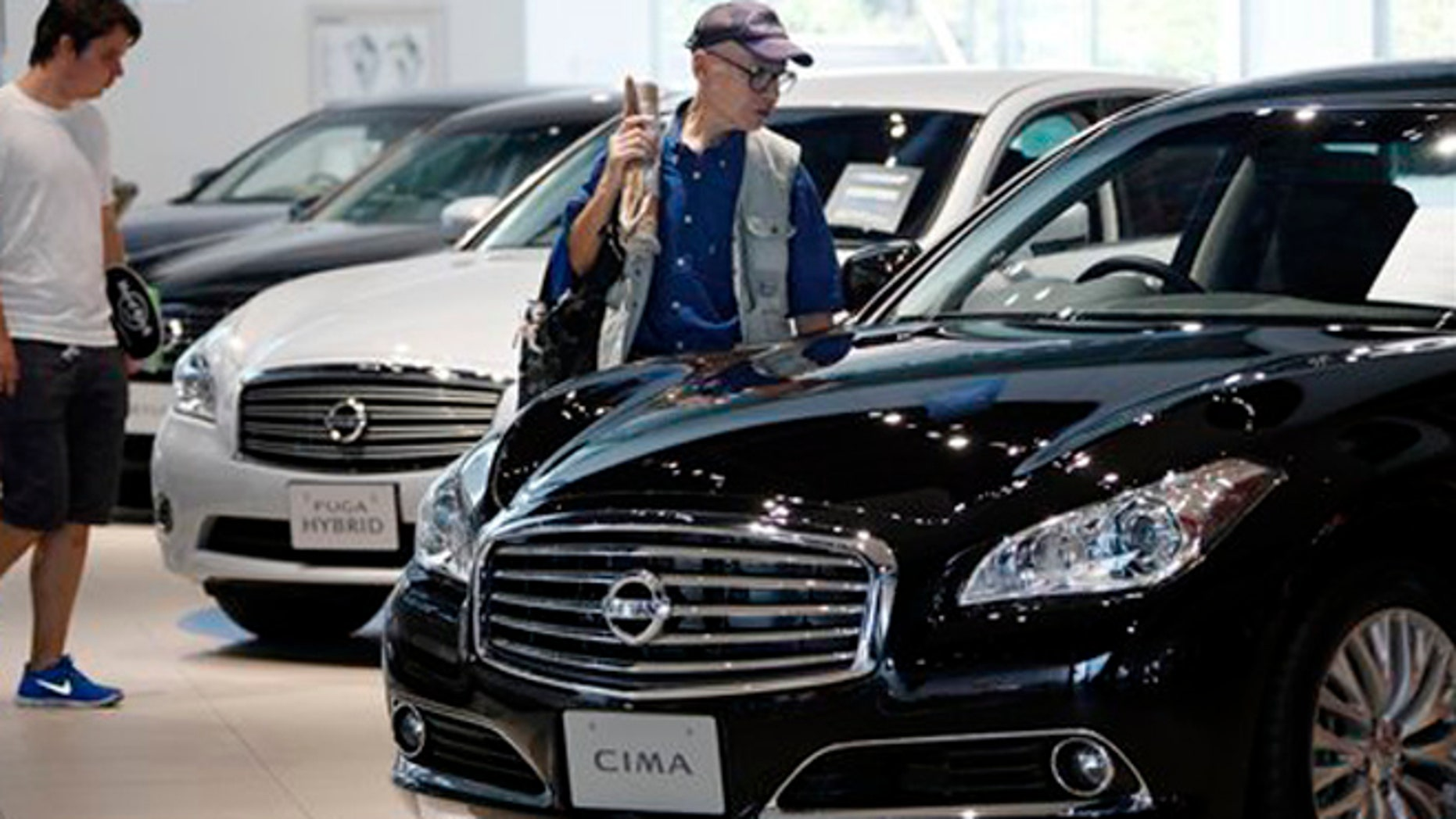 FILE: July 26, 2012: Visitors inspect cars at the Nissan Motor Co. global headquarters in Yokohama, Japan.