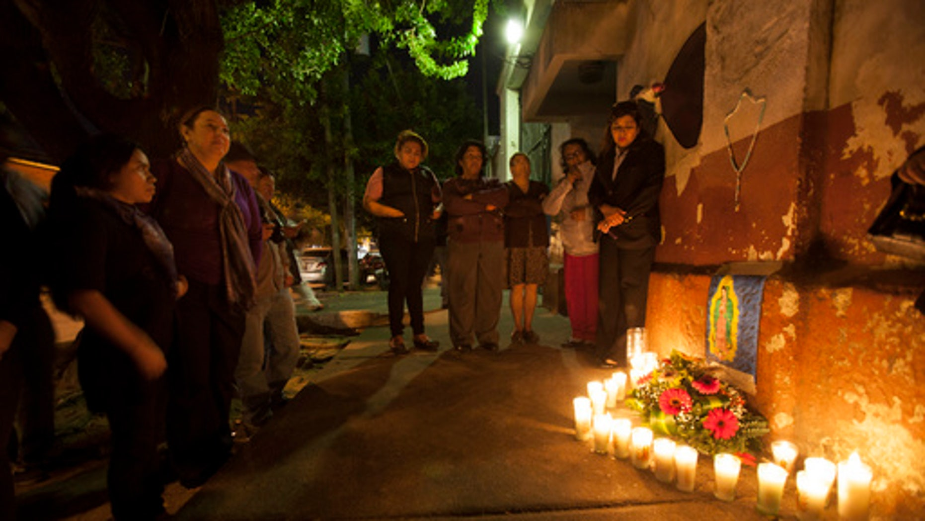 People hold a candlelight vigil in remembrance of the victims of a fire at a children's shelter, outside the morgue where the bodies are being identified in Guatemala City, Wednesday, March 8, 2017.