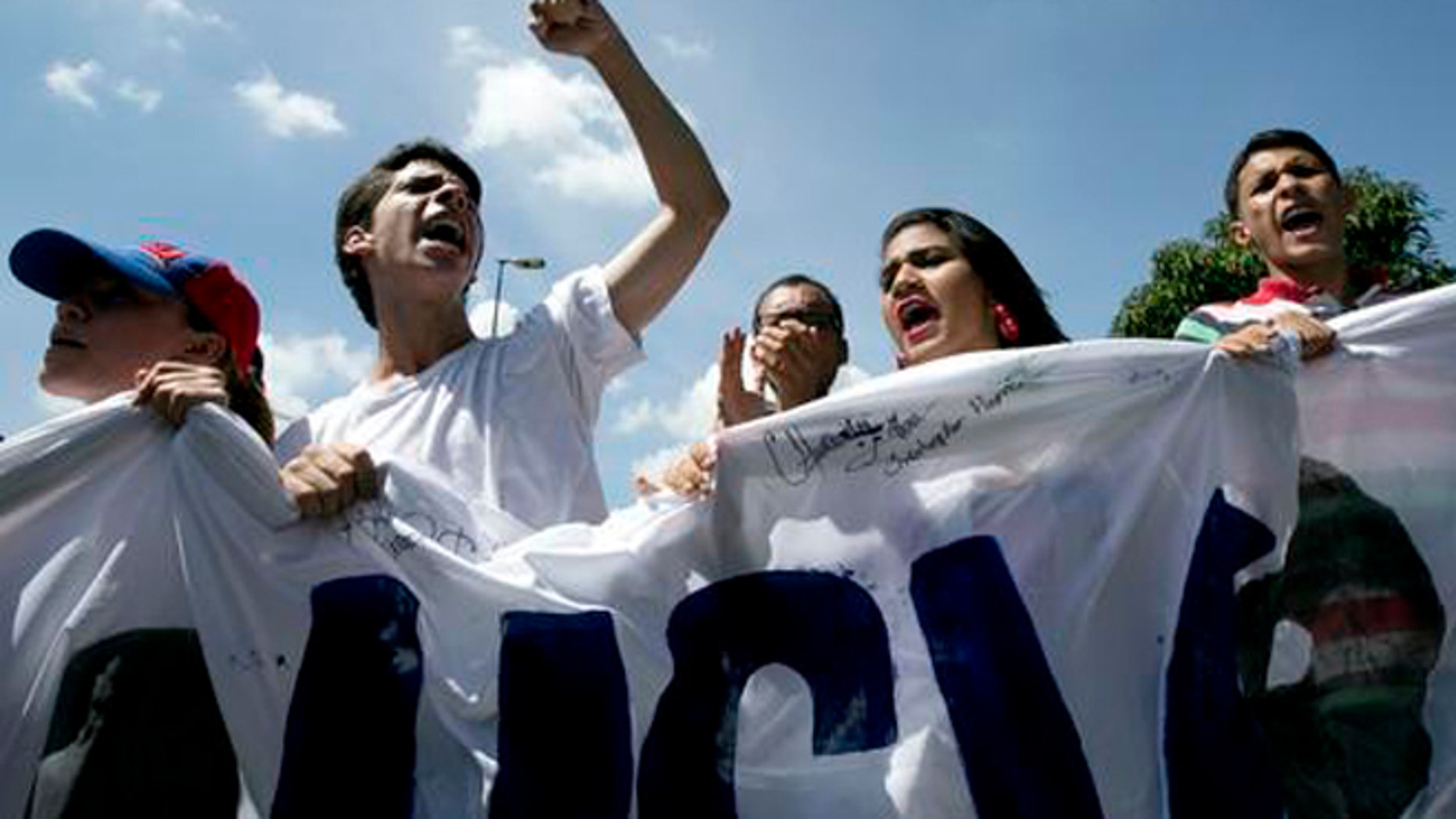 University students protest to demand a recall referendum against Venezuela's President Nicolas Maduro in Caracas, Venezuela, Friday, Oct. 21, 2016. Venezuela's electoral authority suspended a recall drive against Maduro on Thursday, less than a week before it was set to start, throwing the opposition's key campaign to oust the leader into further disarray. (AP Photo/Ariana Cubillos)