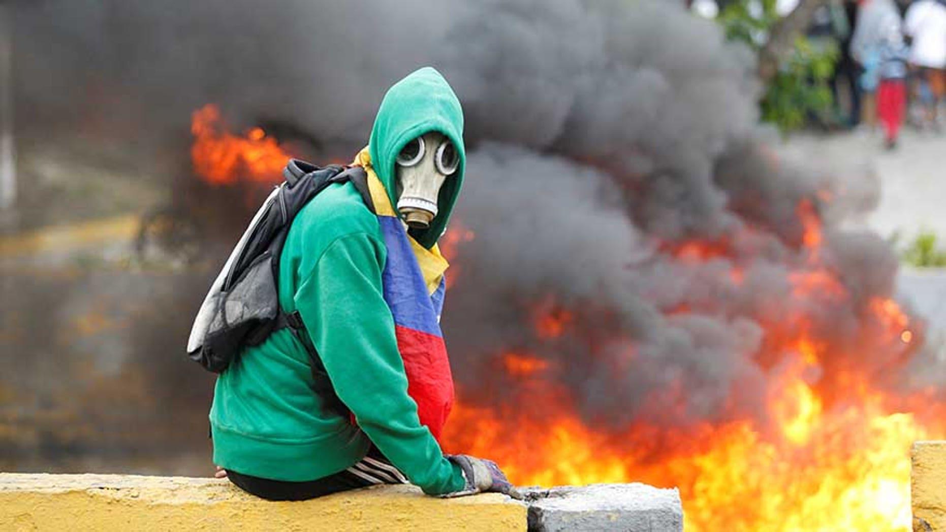 Demonstrator sits next to a fire barricade on a street during a rally against Venezuela's President Nicolas Maduro in Caracas, Venezuela April 24, 2017. REUTERS/Christian Veron - RTS13RH3