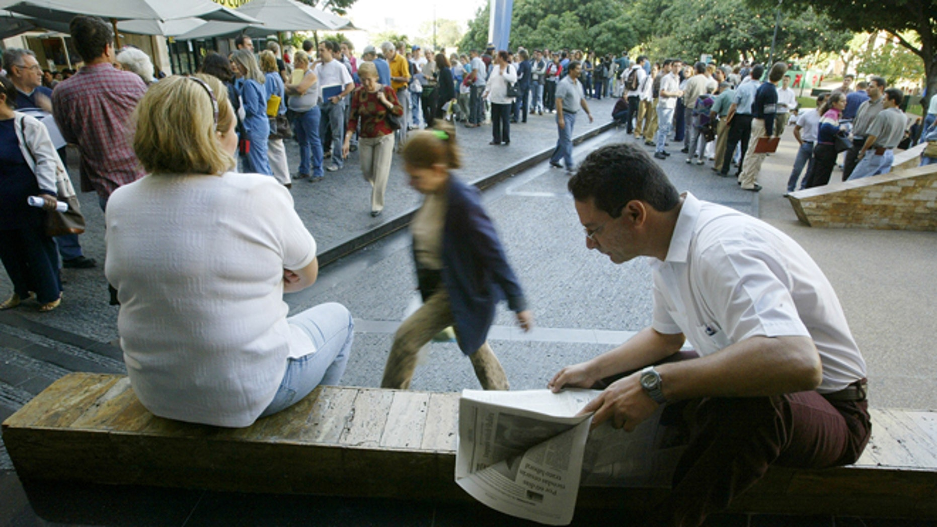 Hundreds of Venezuelans stand in line to apply for a Spanish passport in Caracas, January 10, 2003.