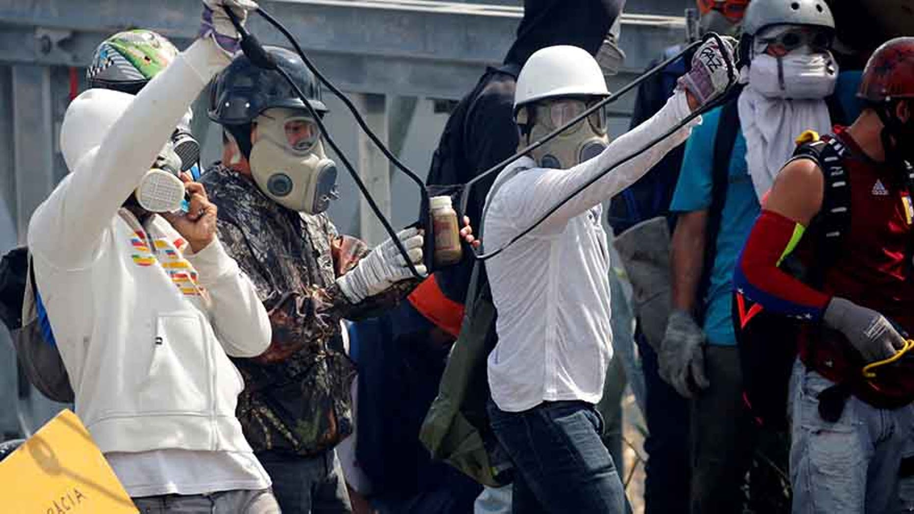 """Opposition supporters use a giant sling shot to throw a """"Poopootov,"""" a bottle filled with feces, which is a play on Molotov, during a rally in Caracas, Venezuela, May 10, 2017."""