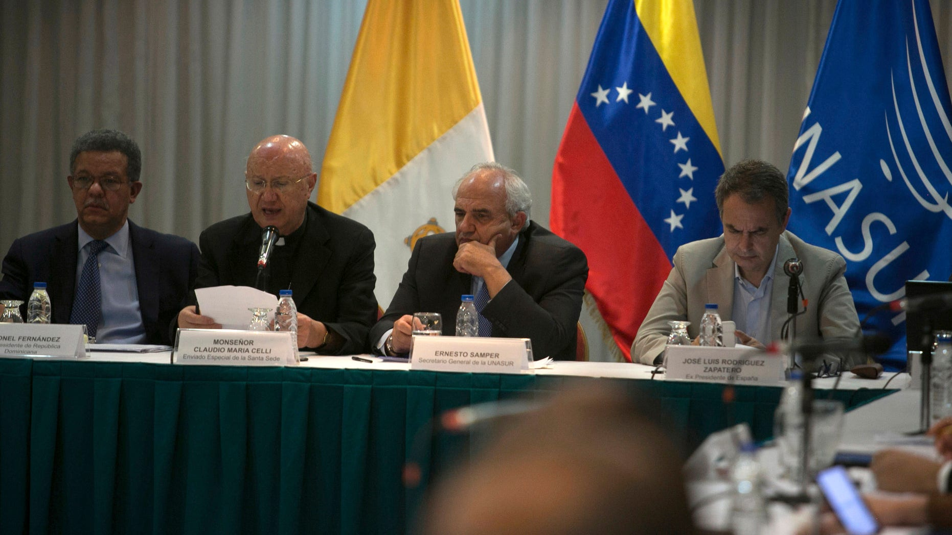 International mediators, from left to right, Dominican Republic's former President Leonel Fernandez, Vatican envoy Archbishop Claudio Maria Celli, Colombian former President Ernesto Samper, and Spain's former Prime Minister Jose Luis Rodriguez Zapatero, sit at the dialogue table between Venezuela's government and its opposition, in Caracas, Venezuela, Friday, Nov, 11 , 2016. The government and the opposition meet on Friday with international mediators to assess the progress of talks aimed at defusing the political crisis in Venezuela following the suspension of the referendum revoking Venezuelan President Nicolas Maduro's term. (AP Photo/Alejandro Cegarra)