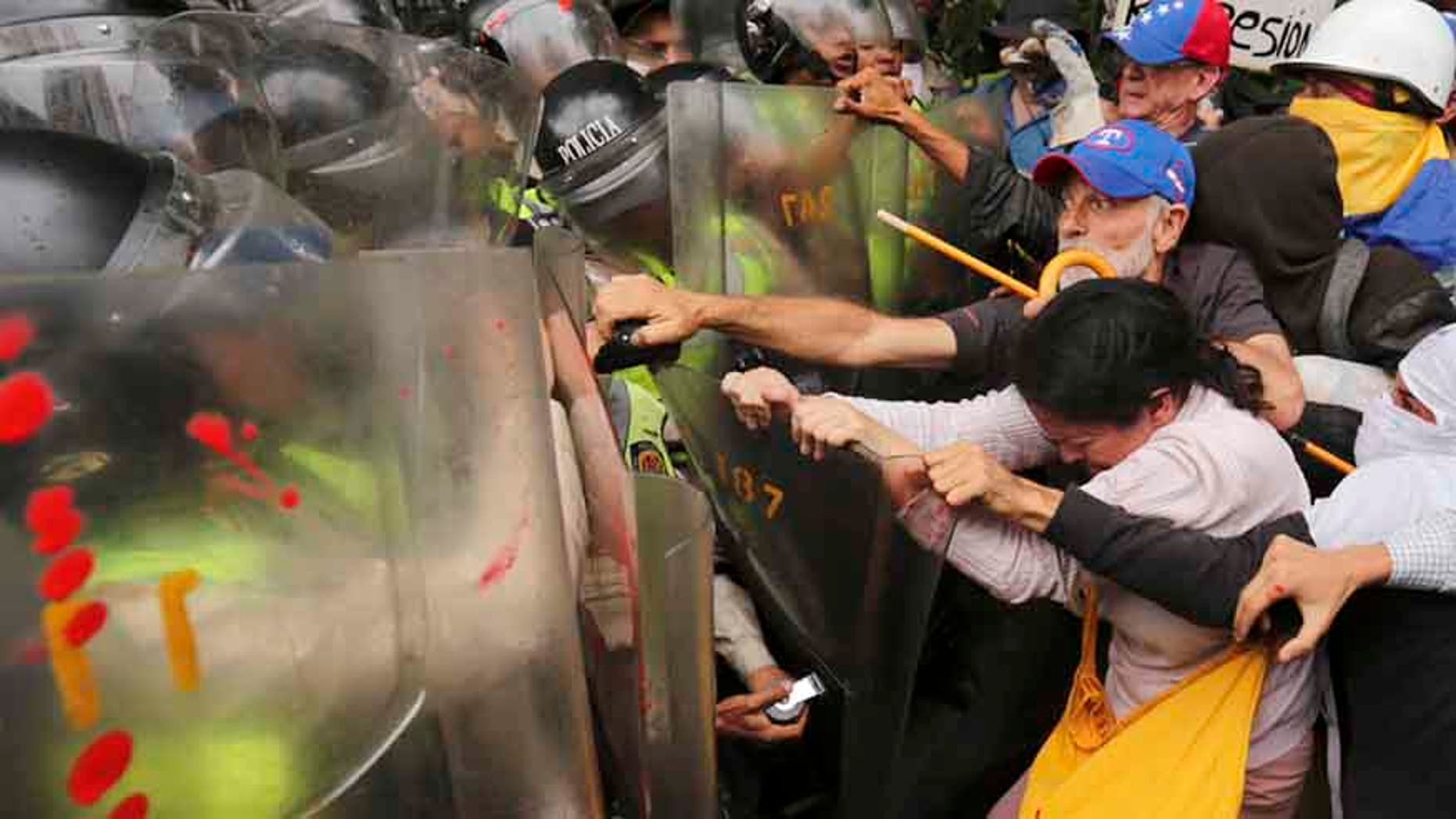 Anti-government protesters scuffle with police blocking older Venezuelans from marching to the Ombudsman's Office in protest of President Nicolas Maduro in Caracas, Venezuela, Friday, May 12, 2017.