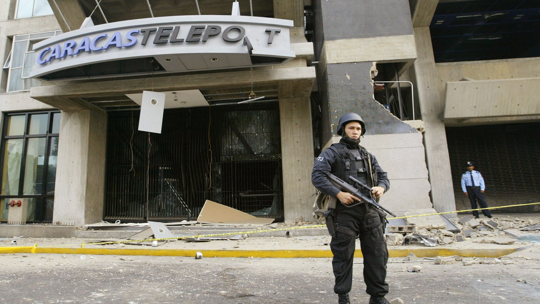 CARACAS, VENEZUELA - APRIL 12:  A police man guards a building where a bomb exploded April 12, 2003 in Caracas, Venezuela. A bomb ripped through a building where government and opposition negotiators had agreed to hold a referendum on President Hugo Chavez. This blast follows several other bomb explosions in the last six weeks and falls on the year anniversary of a brief coup attempt against President Chavez. (Photo by Kimberly White/Getty Images)