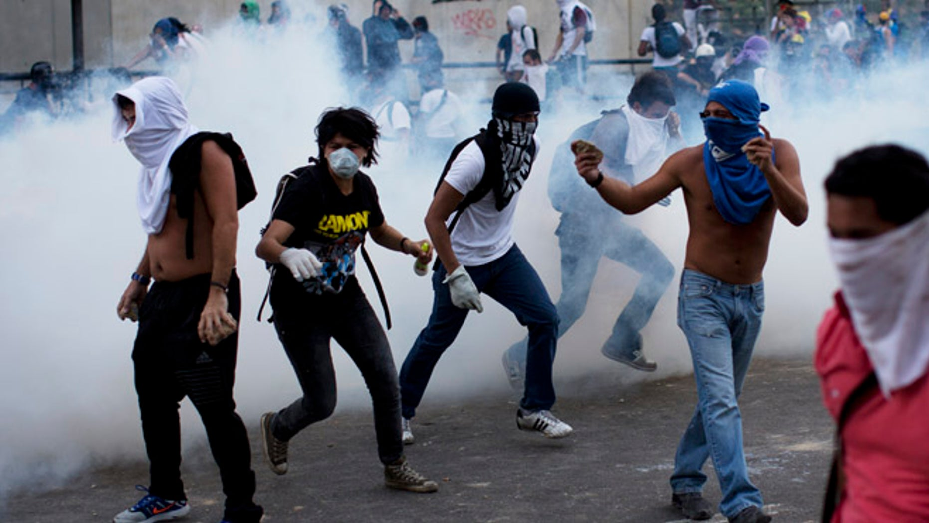 Feb. 22, 2014: A group of masked men run for cover after riot police launched tear gas in Caracas, Venezuela.
