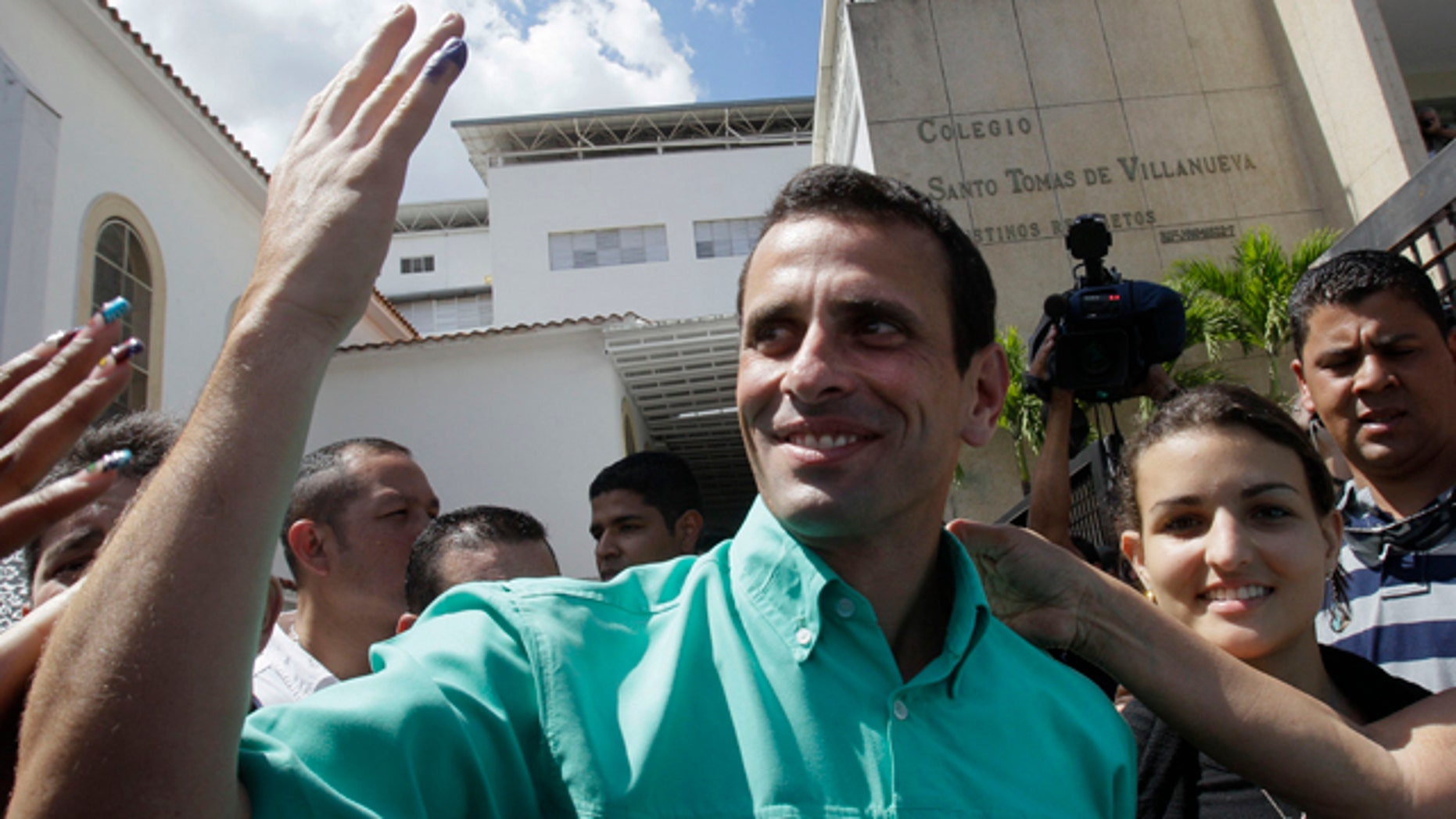 Feb. 12, 2012: Henrique Capriles, the front-runner among five opposition presidential contenders, shows off his ink-stained pinky as he leaves a polling station in Caracas, Venezuela.