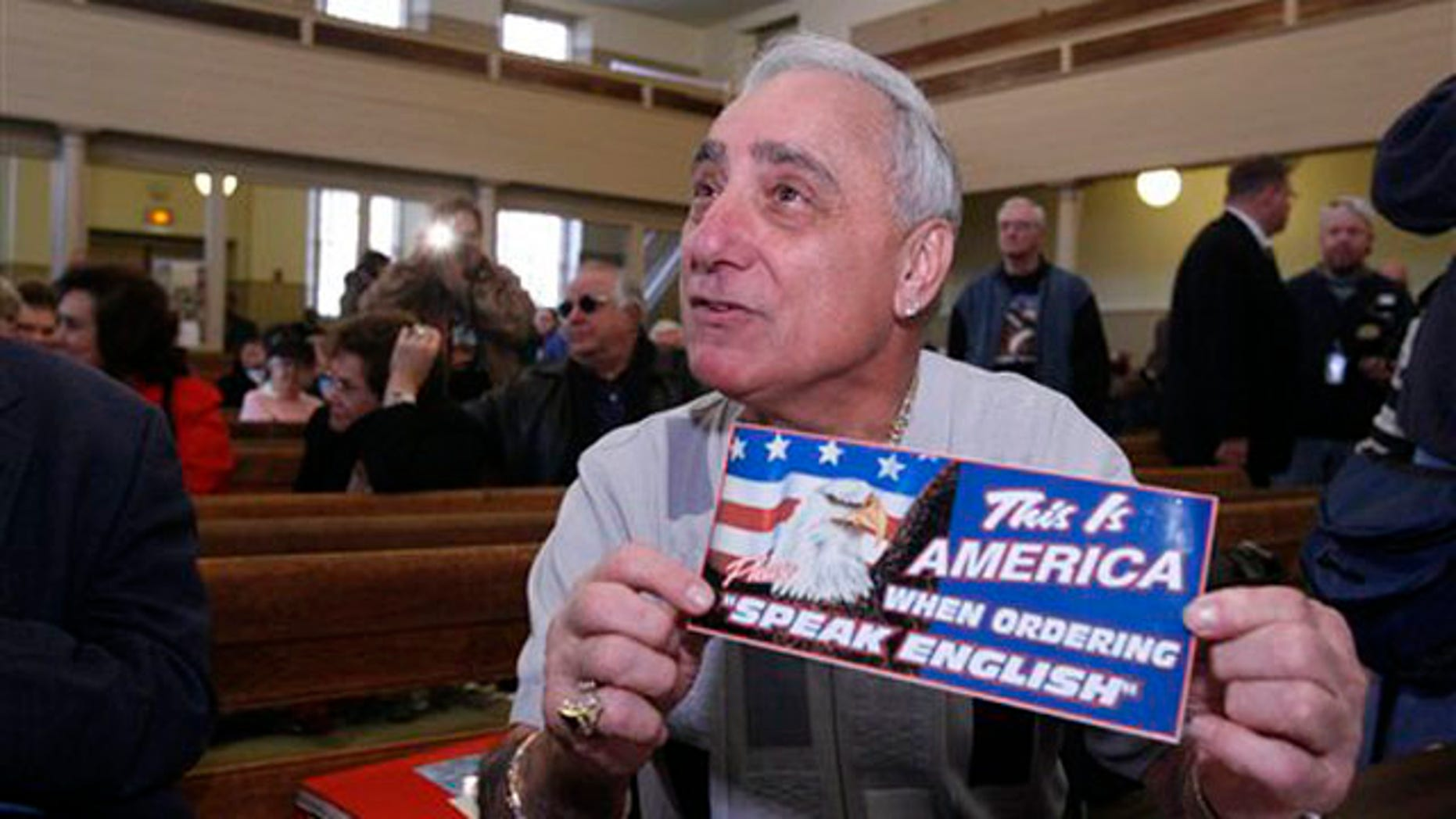 In this Dec. 14, 2007 file photo, Joey Vento, owner of Geno's Steaks, displays a sign during a recess of a Commission on Human Relations hearing in Philadelphia.