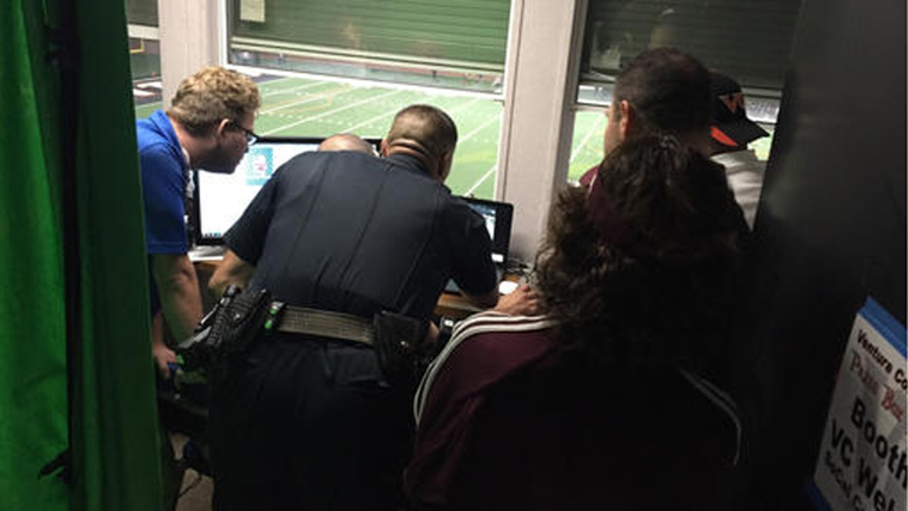 Ventura College police officer reviews game footage to determine whether a Mt. St. Antonio College football player punched a referee during a game Saturday. (Joe Curley/The Ventura County Star via AP)