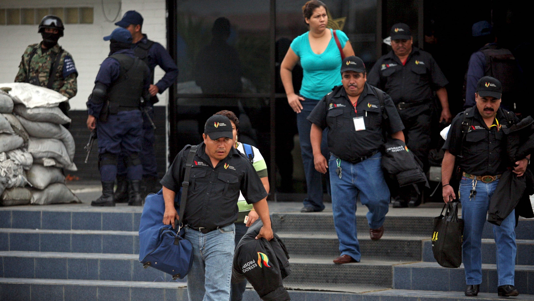 Municipal policemen leave a police station after the entire police force was disbanded in the Gulf port city of Veracruz, Mexico, Wednesday Dec. 21, 2011. The Veracruz state government said the decision is part of an effort to root out police corruption and start from zero in the state's largest city. The navy will be in charge of patrolling the city for the time being. (AP Photo/Felix Marquez)