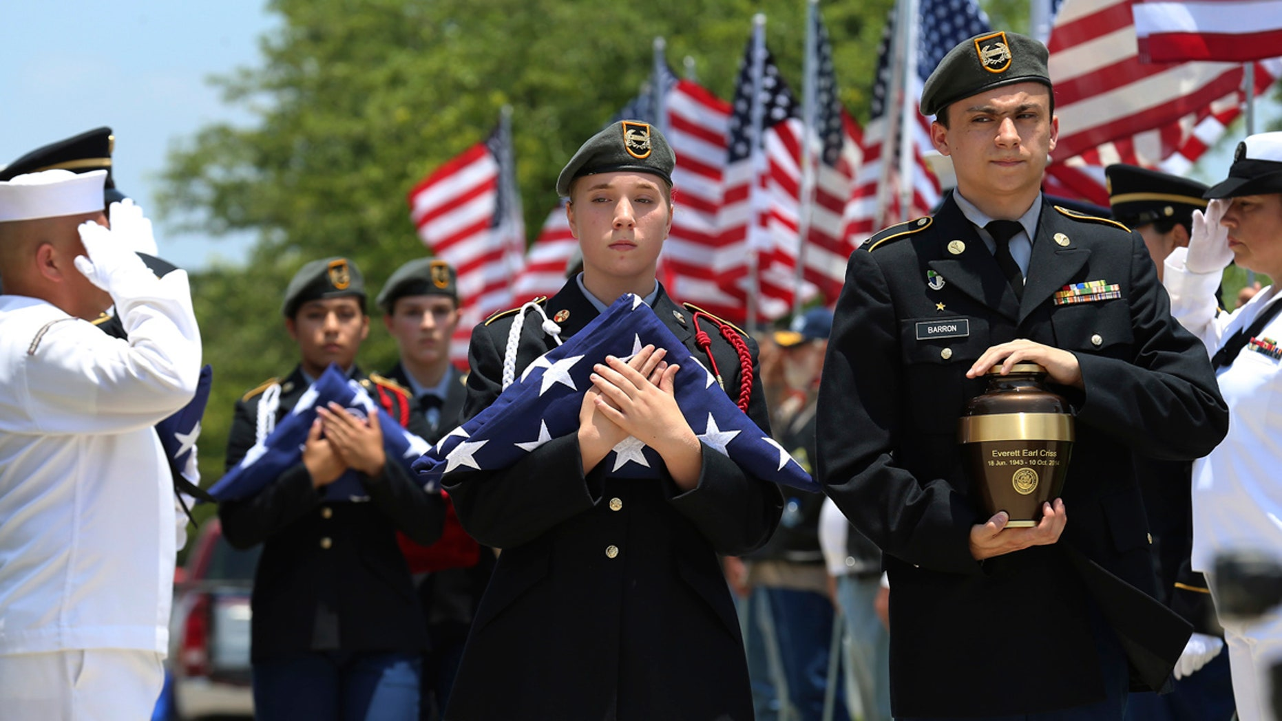 In this Friday, June 1, 2018 photo, MacArthur Junior ROTC students Michael Barron, right, and Grace Conger carry the cremated remains of veteran Everett Earl Criss as Fort Sam Houston National Cemetery and the Missing In America Project conduct a military burial service for the cremated remains of eight unclaimed veterans in San Antonio, Texas.