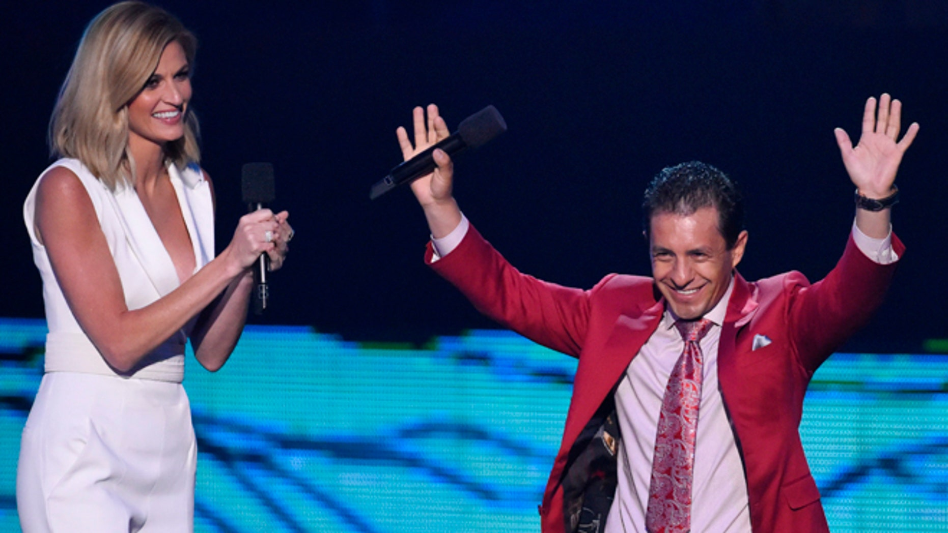 Triple Crown winning jockey Victor Espinoza, who rode American Pharoah, is introduced by show co-host Erin Andrews during the 2015 CMT Awards in Nashville, Tennessee June 10, 2015. REUTERS/Harrison McClary - RTX1G0BV