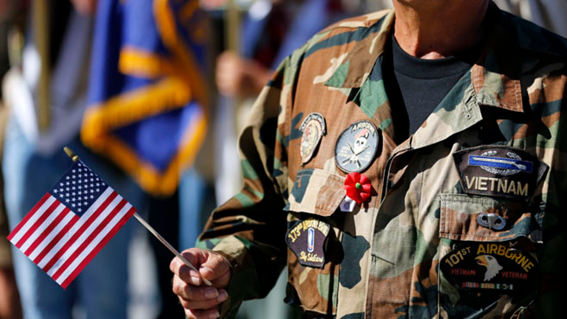 Nov. 11, 2013: A Vietnam veteran holds an American flag as he marches during the annual Veterans Day Parade in San Diego, Calif.