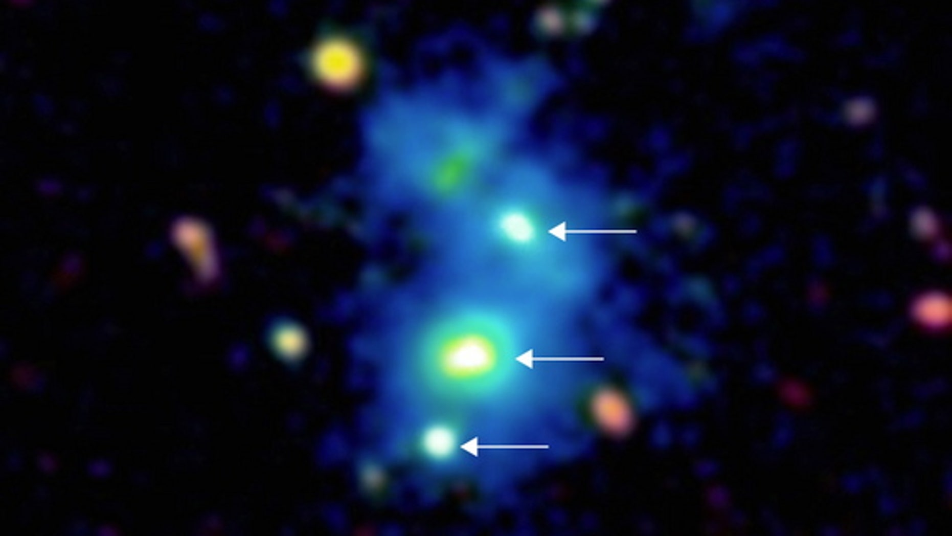 This image shows a rare view of four quasars, indicated by white arrows, found together by astronomers using the Keck Observatory in Hawaii. The bright galactic nuclei are embedded in a giant nebula of cool, dense gas visible in the image as a