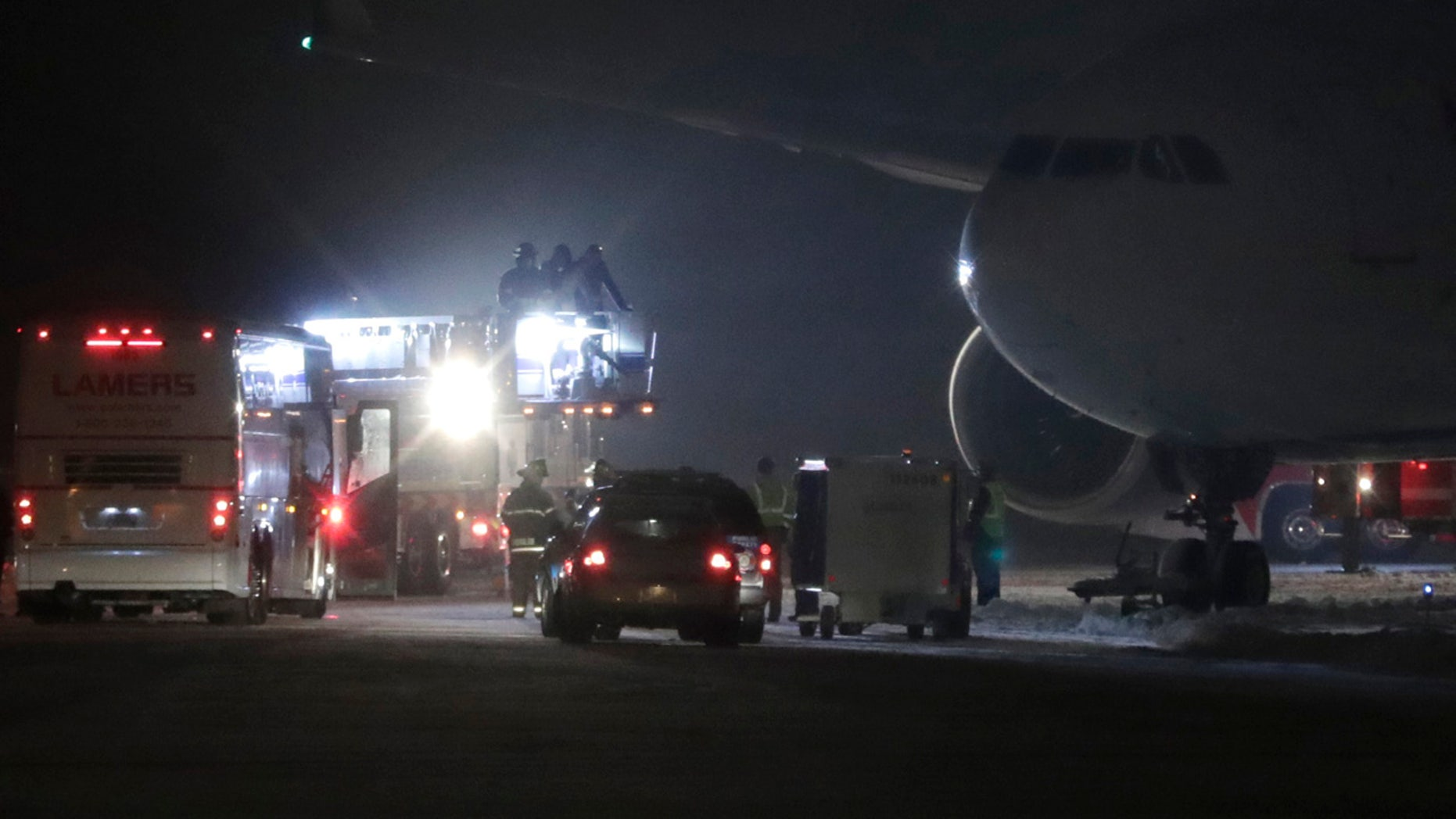Players, coaches and staff from the Minnesota Vikings are taken off a plane in small groups at Appleton International Airport on Friday, Dec. 23, 2016, in Appleton, Wis.