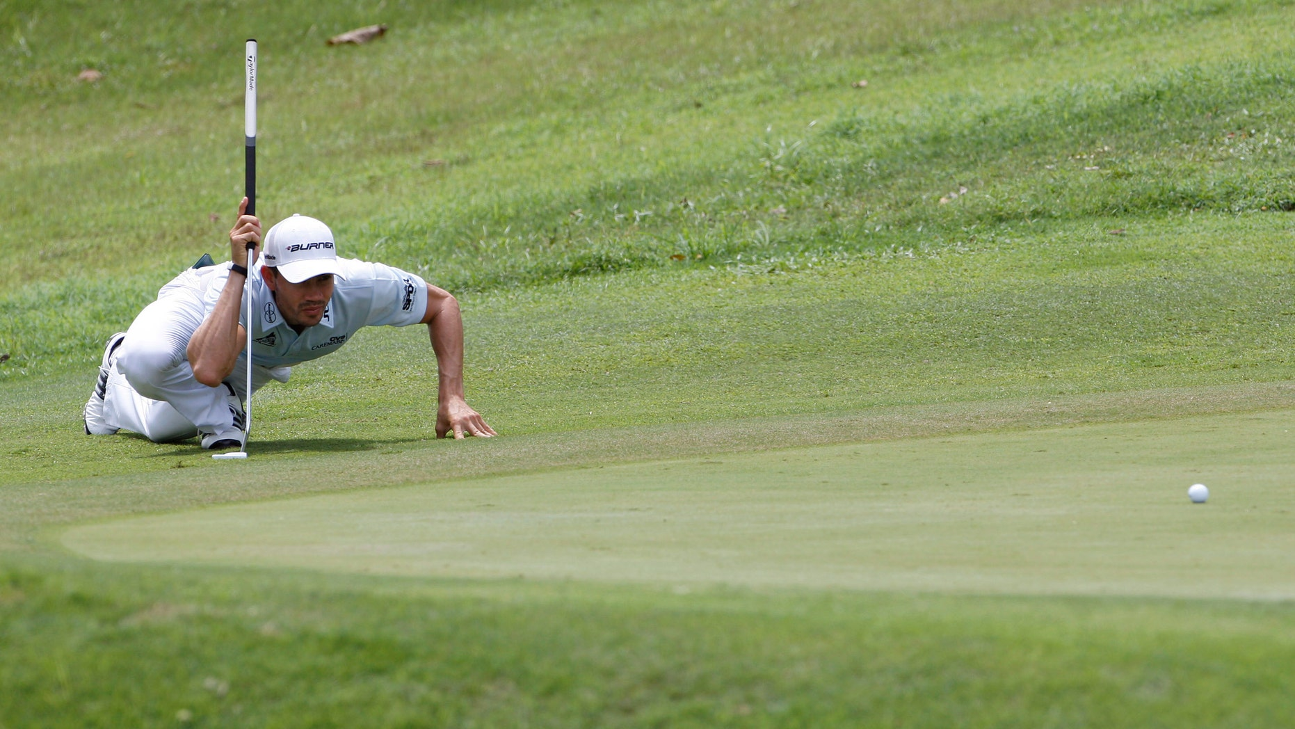 Camilo Villegas of Colombia lines up his putt on the 8th green during the third round of the Asia Pacific Classic Malaysia golf tournament at The Mines Resort & Golf Club in Kuala Lumpur, Malaysia, Saturday, Oct. 29, 2011. (AP Photo/Lai Seng Sin)