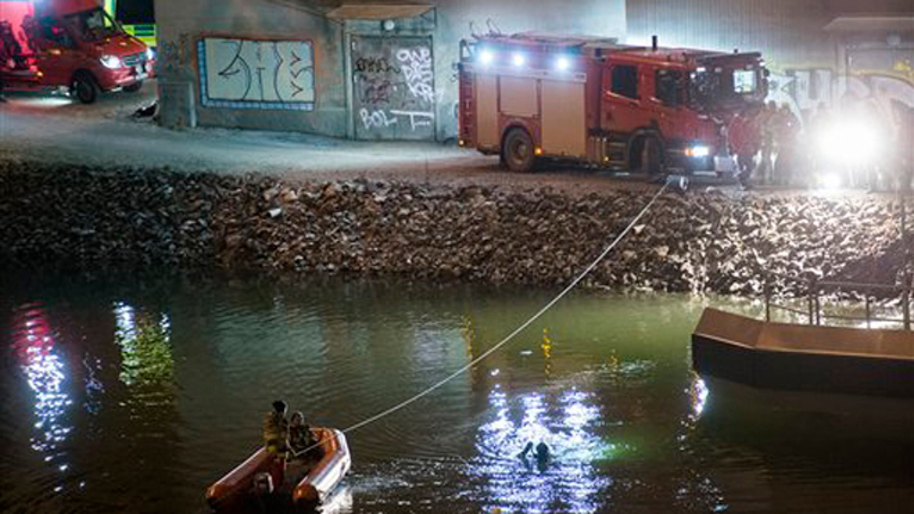 Divers and rescue service personnel search for the victims of the deadly car crash in the canal under the E4 highway bridge in Sodertalje, Sweden, late Saturday, Feb.13, 2016.  (Johan Nilsson/TT News Agency via AP)