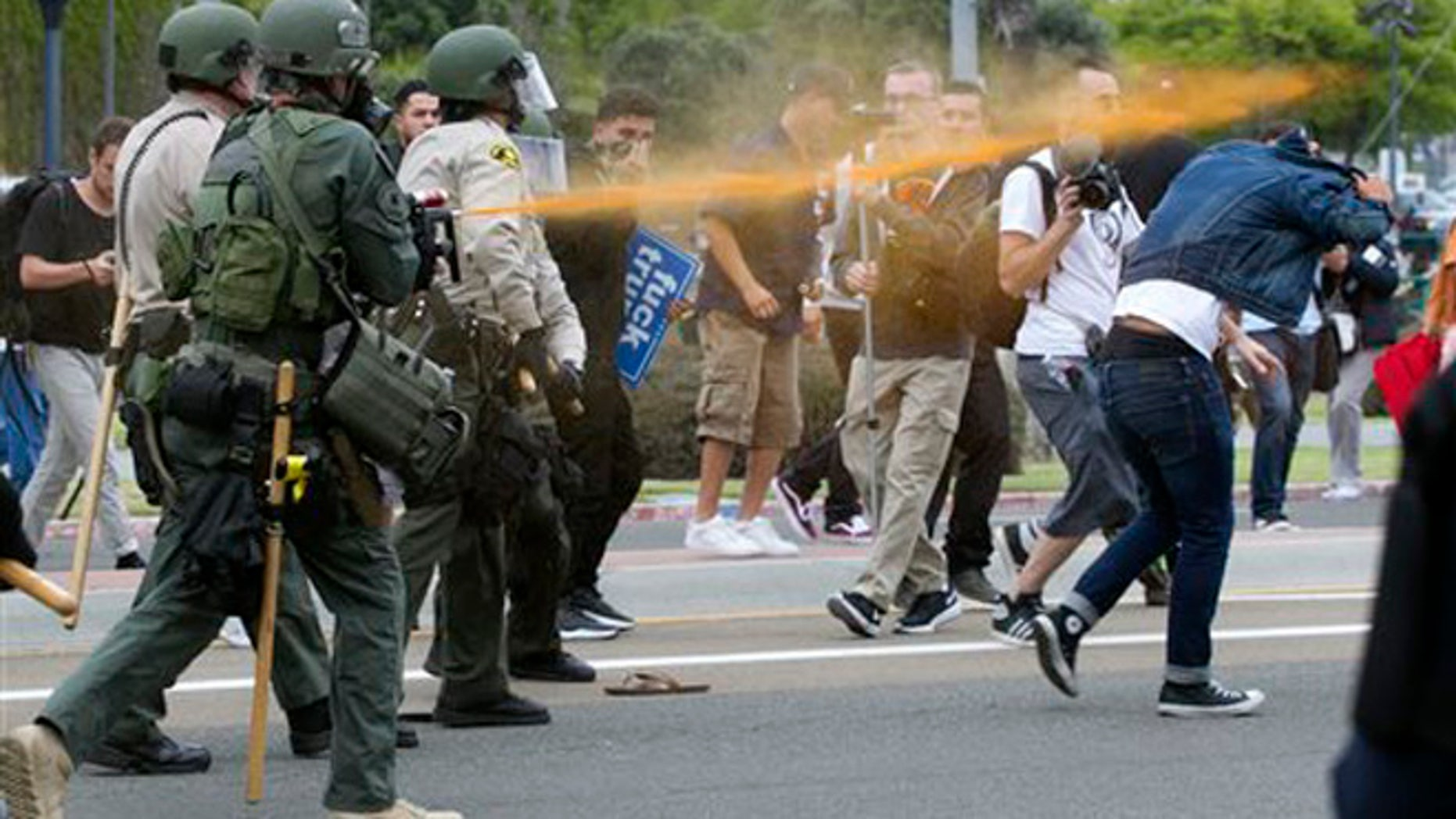 Police pepper sprayed protesters as they moved them down Harbor Drive in San Diego Friday, May 27, 2016. About a thousand Trump protesters demonstrated outside San Diego's convention center as Republican presidential candidate Donald Trump spoke inside to an enthusiastic crowd of supporters packed in tight. Several protesters were arrested.  (John Gibbins/The San Diego Union-Tribune via AP)  NO SALES; MANDATORY CREDIT