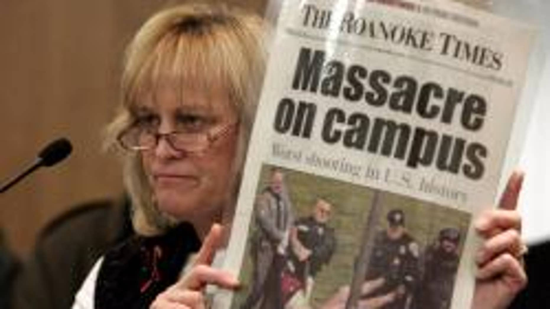 In this Jan. 21, 2008, file photo Suzanne Grimes holds up a picture of her injured son, Virginia Tech shooting victim Kevin Sterne, during a Senate Courts of Justice committee hearing on a bill to close the gun show loophole at the Capitol in Richmond, Va.