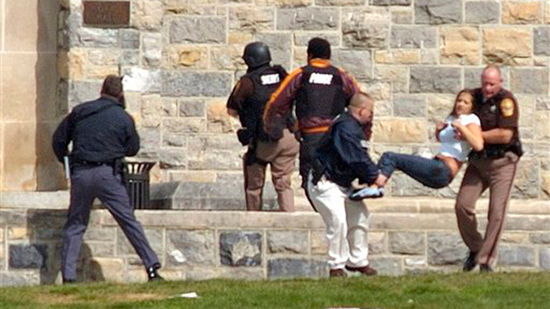 In this April 16, 2007 file photo, injured occupants are carried out of Norris Hall at Virginia Tech in Blacksburg, Va., where student gunman Seung-Hui Cho went on a shooting rampage that left 33 dead, including himself.