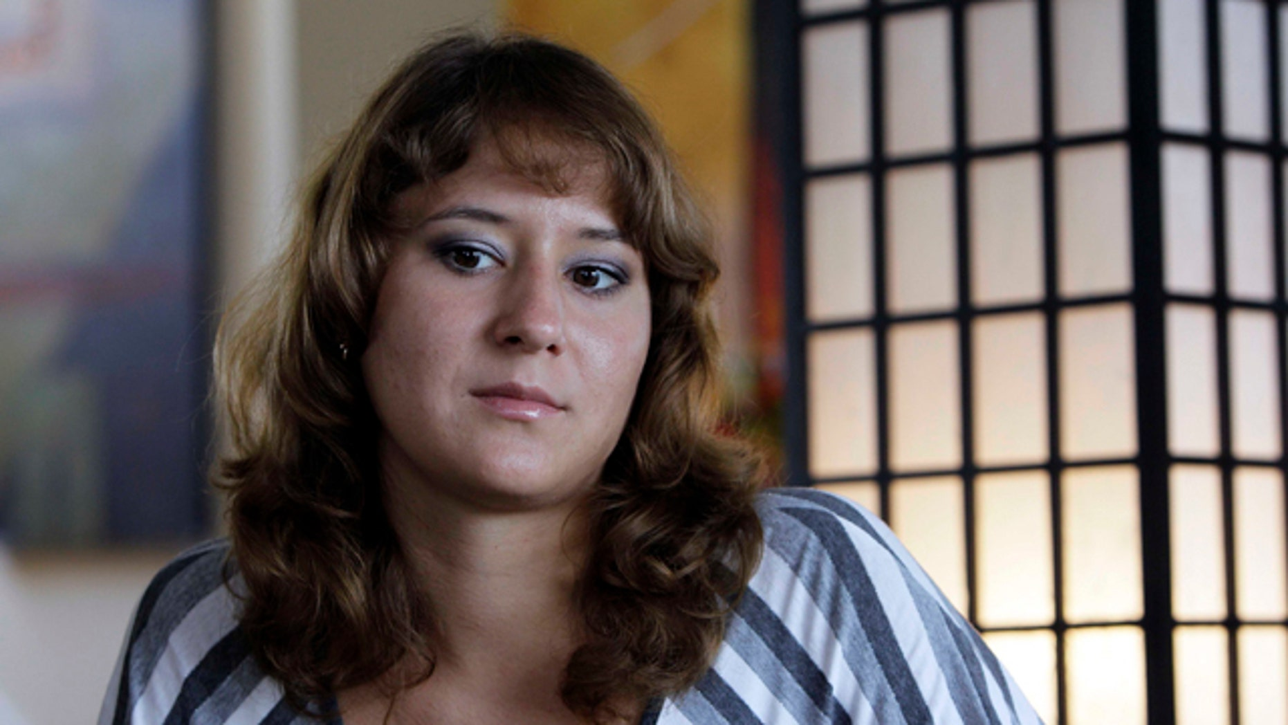 Aug. 24, 2010: Iuliia Bolgaryna sits for an interview in Surf City, N.C. Bolgaryna came to work on a J-1 visa at a souvenir store in Surf City, N.C. The store manager offered to let her and two other women from the Ukraine stay with him for $120 a week. But he wouldn't let them eat at the table, so they huddled together for meals on the floor. They worked loads of overtime but were only paid for 40 hours a week. (AP)