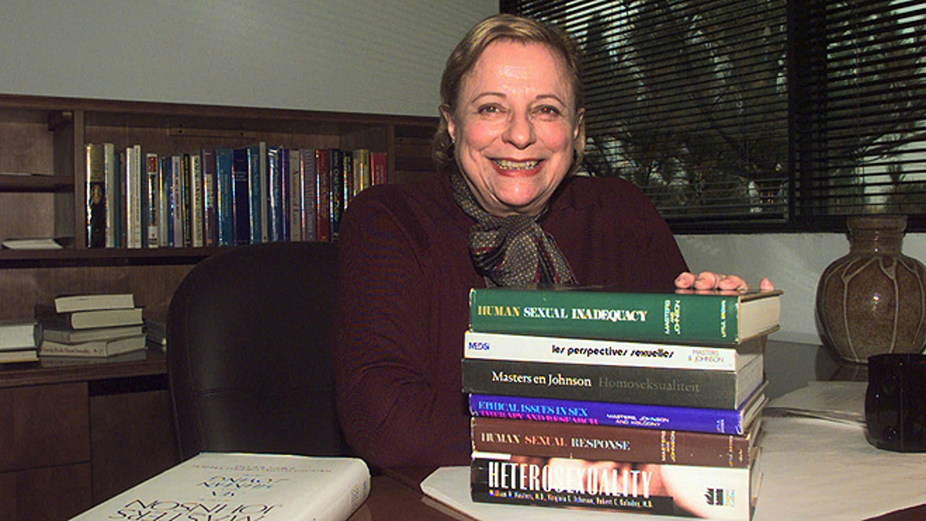 Nov. 7, 1997: Virginia Johnson Masters poses in her office at the Virginia Johnson Masters Learning Center in Creve Coeur, Mo., with some of the 19 publications that she has written or co-authored with her former husband and former partner Dr. William Masters. (AP/James A. Finley, File)