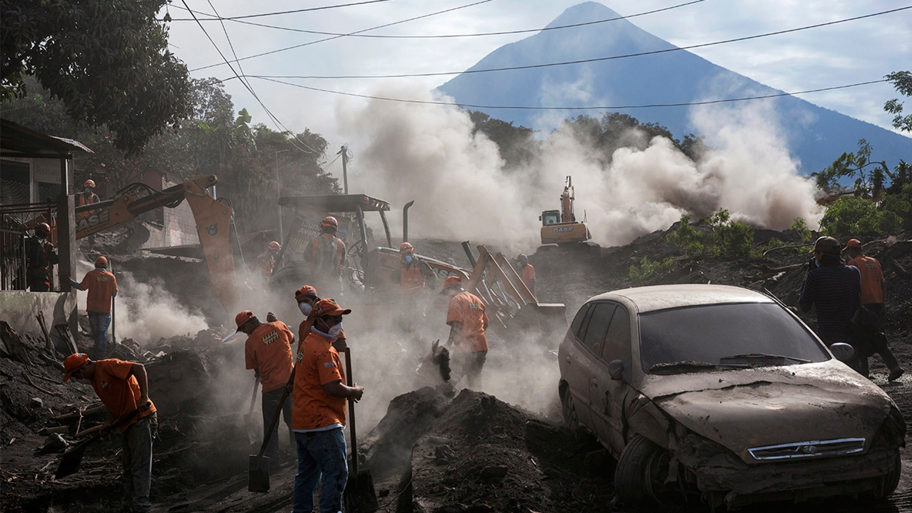 "Rescue workers remove piles of ash spewed by the Volcan de Fuego, or ""Volcano of Fire,"" eruption, in El Rodeo, Guatemala, Wednesday, June 6, 2018. Wednesday morning rescuers were concerned about possible dangers posed not only by more volcanic flows but also rain. Authorities have said the window is closing on the chances of finding anyone else alive in the devastation. (AP Photo/Rodrigo Abd)"