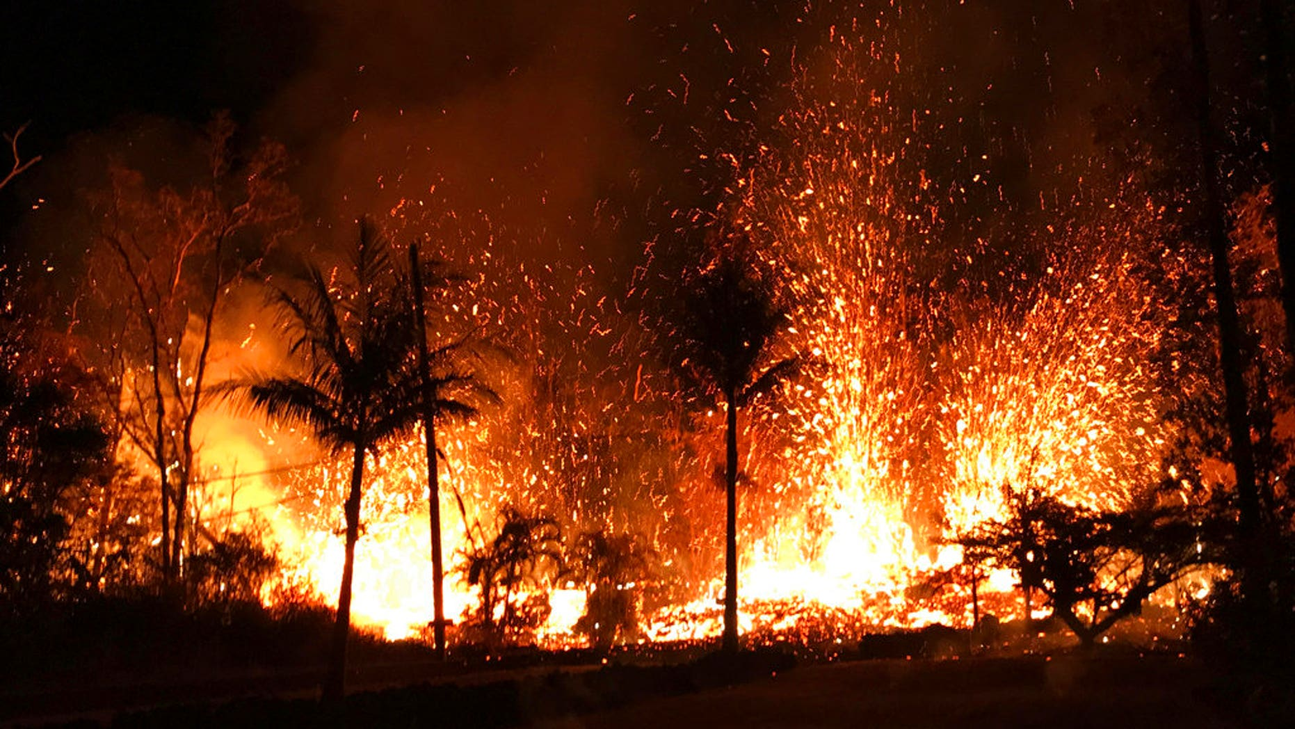In this Saturday, May 5, 2018 photo, a new fissure erupts in Leilani Estates in Pahoa, Hawaii. Hawaii's erupting Kilauea volcano has destroyed homes and forced the evacuations of more than a thousand people. (U.S. Geological Survey via AP)