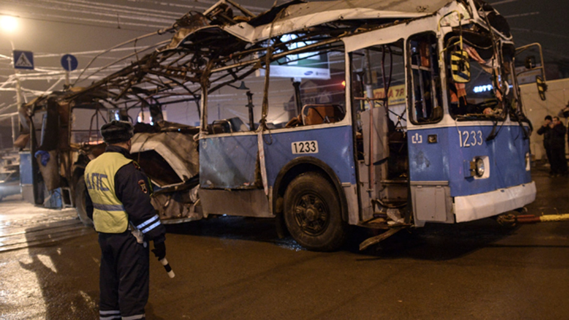 Dec. 30, 2013: A policeman watches as a bus, destroyed in an earlier explosion, is towed away in Volgograd.