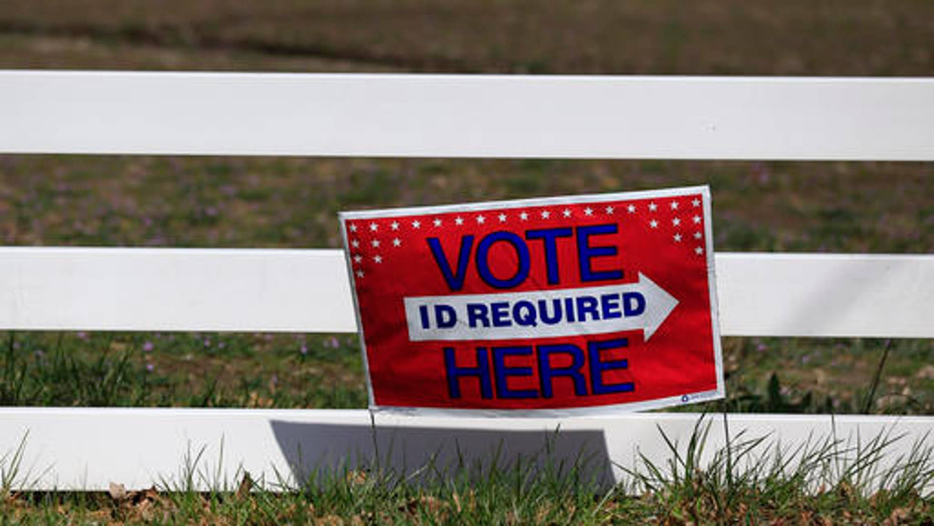 A sign directing voters is posted along a fence line at the Platte County Fair Grounds in Tracy, Mo., Tuesday, March 15, 2016. Voters in Missouri, as well as North Carolina, Illinois, Ohio and Florida are casting their ballots in primary elections Tuesday. (AP Photo/Orlin Wagner)