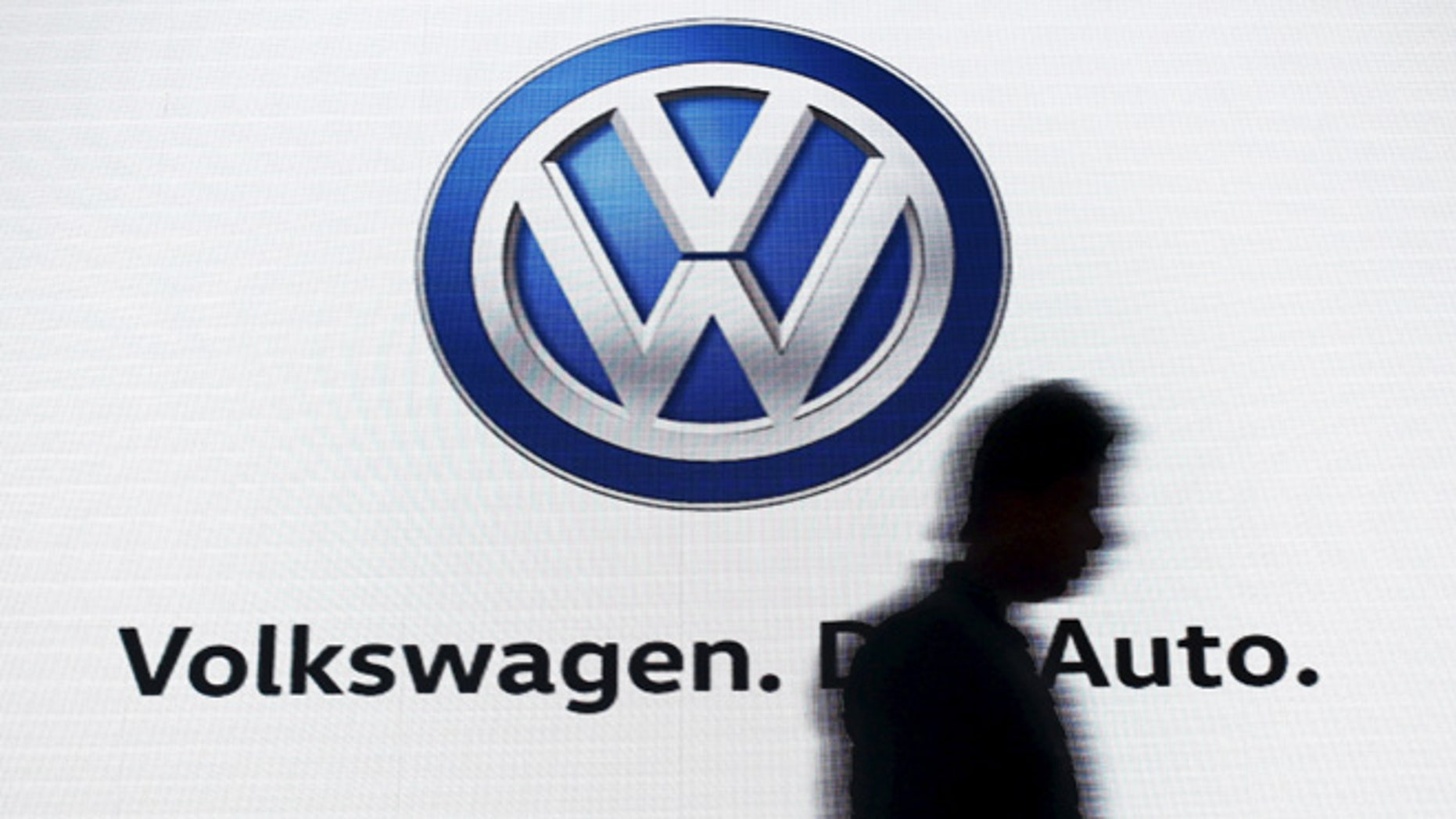 June 23, 2015: A man walks past a screen displaying a logo of Volkswagen at an event in New Delhi, India. (Reuters)