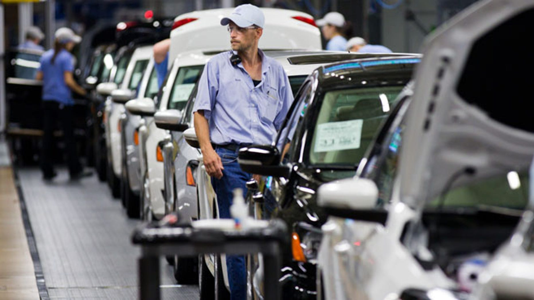In this July 31, 2012 photo, an employee at the Volkswagen plant in Chattanooga, Tenn., works on a Passat sedan. Martin Winterkorn, the German automaker's CEO, said on Tuesday, Oct. 23, 2012, that Volkswagen is considering the production of a new midsize SUV for the North American market, and that the Tennessee facility would be in the running to make the model. (AP Photo/Erik Schelzig)