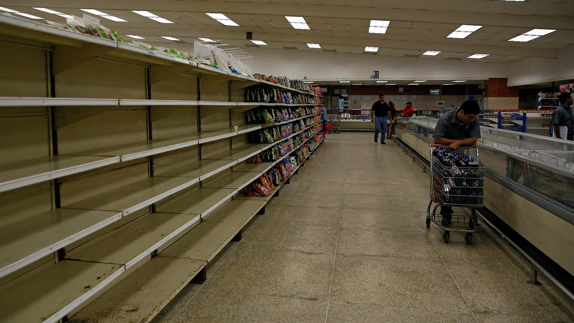 People buy food and other staple goods inside a supermarket in Caracas, Venezuela June 30, 2016.