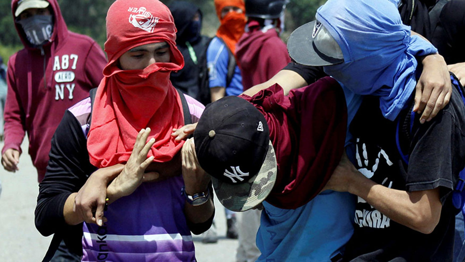 Demonstrators attend to a fellow protester during a protest against Venezuela's government in San Cristobal, Venezuela, April 6, 2017.