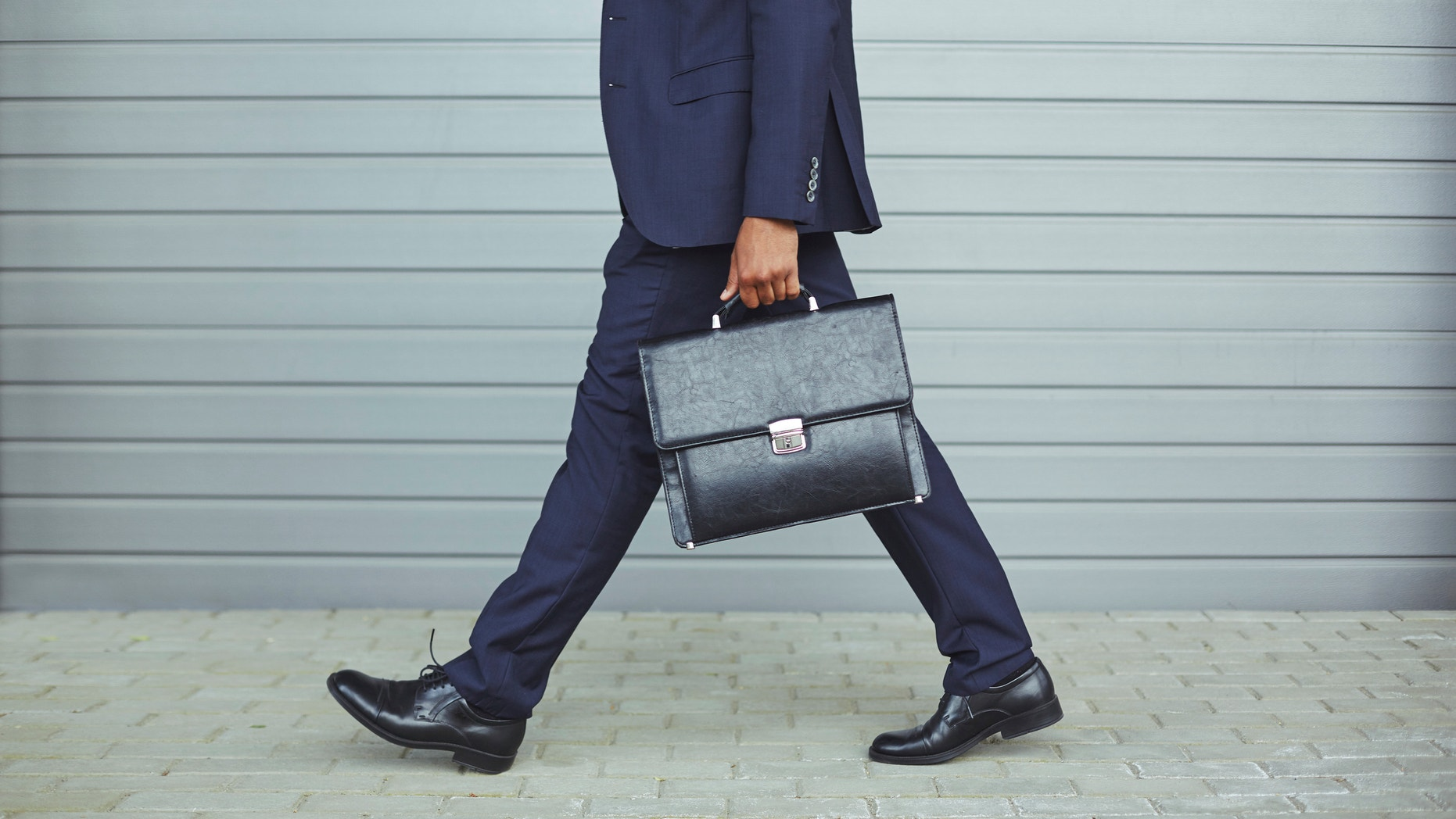 Legs of businessman in suit walking to work in the morning