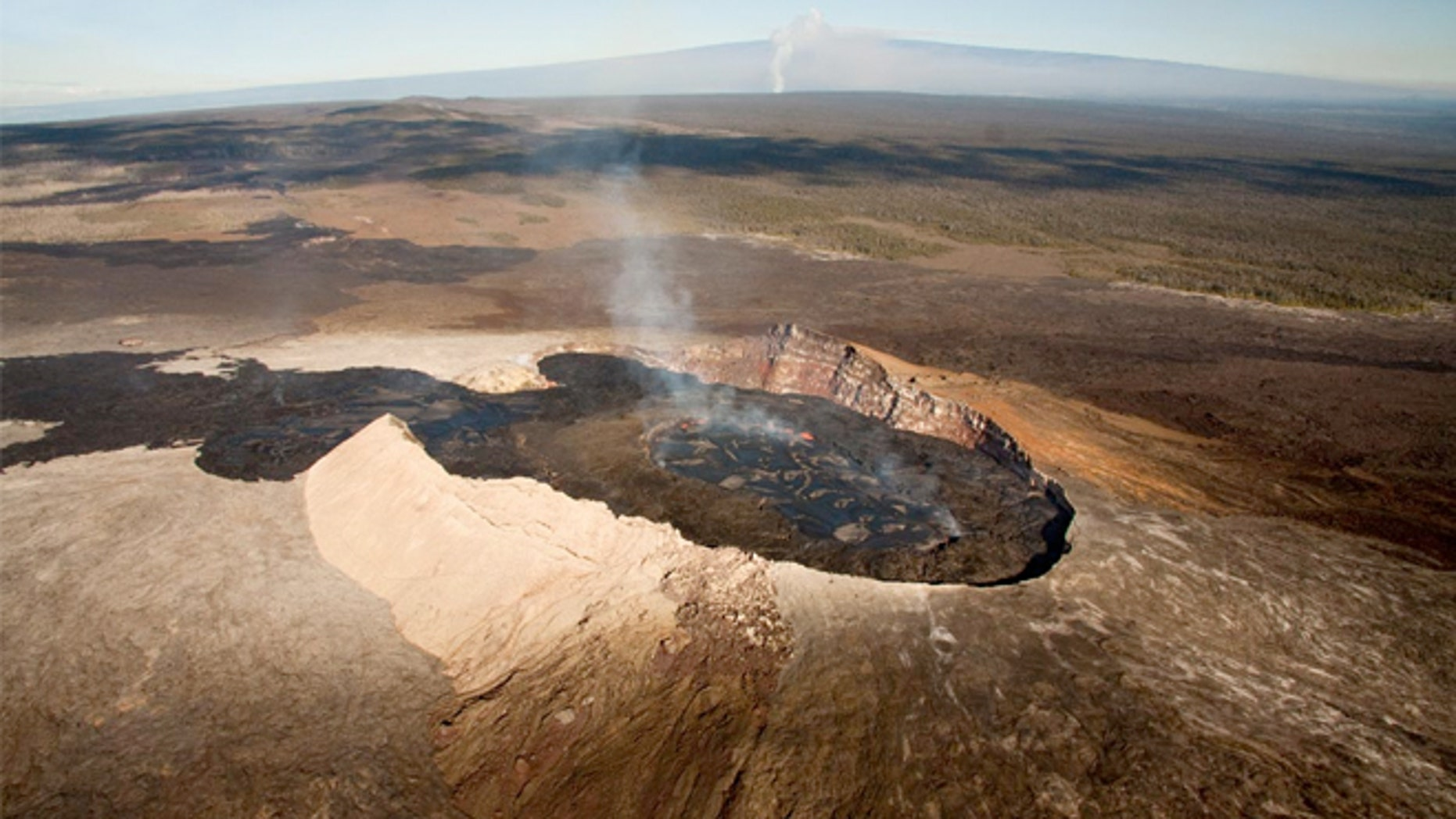 The Halemaumau crater is at the peak of Kilauea, visible here as a rising ash column in the background.