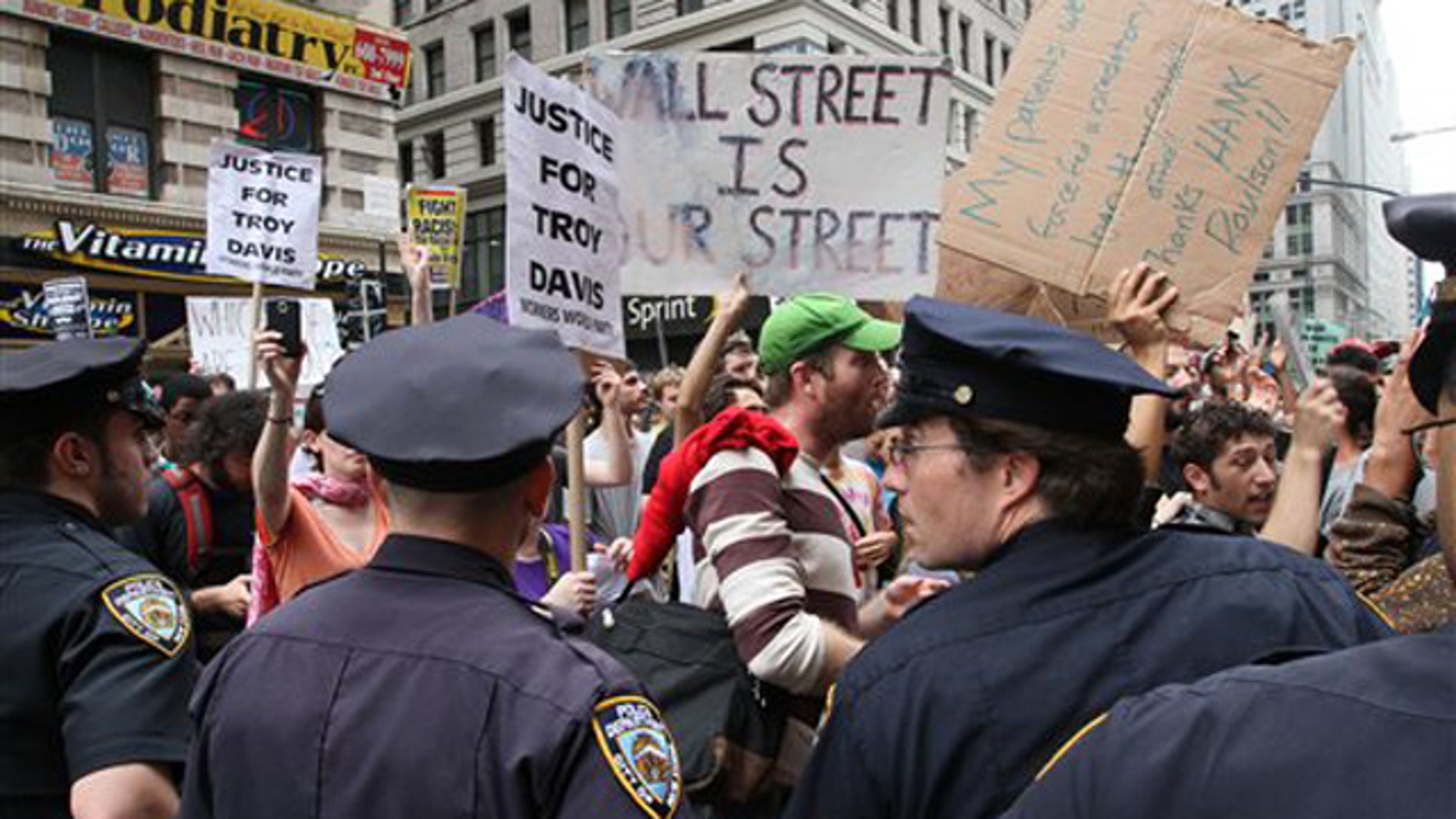 Participants in a march organized by Occupy Wall Street make their up Broadway as police stand by Saturday Sept. 24, 2011 in New York.