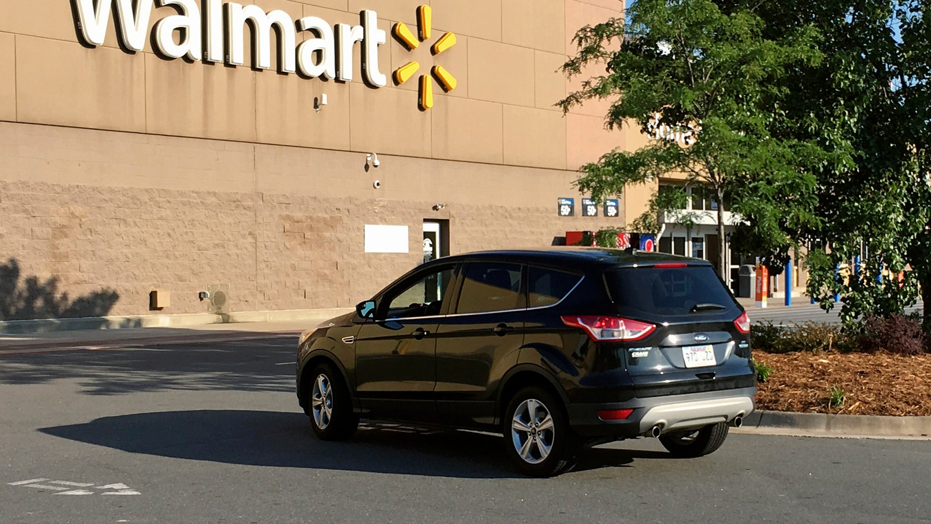 A motorist drives through a Walmart parking lot in west Little Rock, Ark., Wednesday, June 28, 2017. The company was hosting hundreds of potential vendors at its Bentonville headquarters on Wednesday, searching for products to someday stock on store shelves. (AP Photo/Kelly P. Kissel)