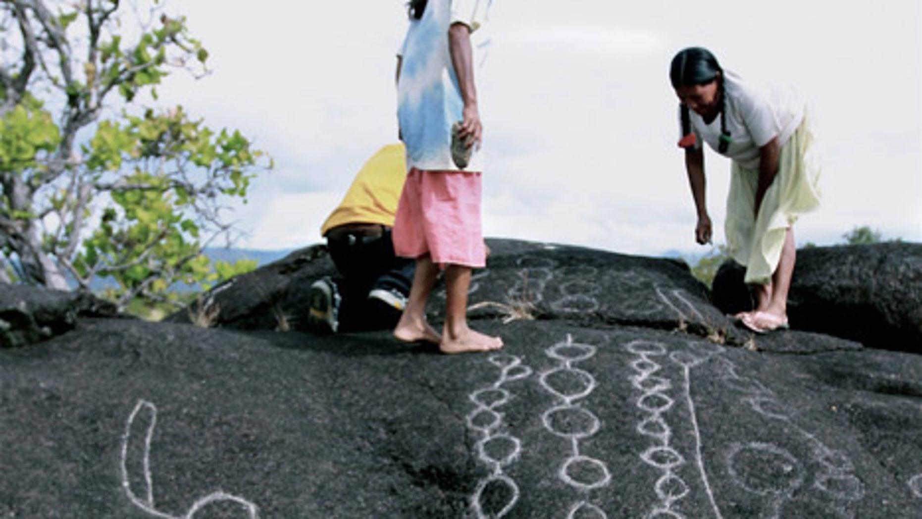 Two Wapishana women maintain traditional rock carvings at a spiritual site.