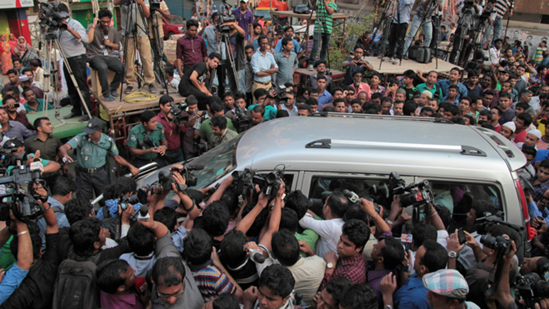Apr. 11, 2015: Journalists surround the car carrying family members of Mohammad Qamaruzzaman, an assistant secretary general of Jamaat-e-Islami party, as they leave the Central Jail after meeting Qamaruzzaman in Dhaka, Bangladesh.(AP)