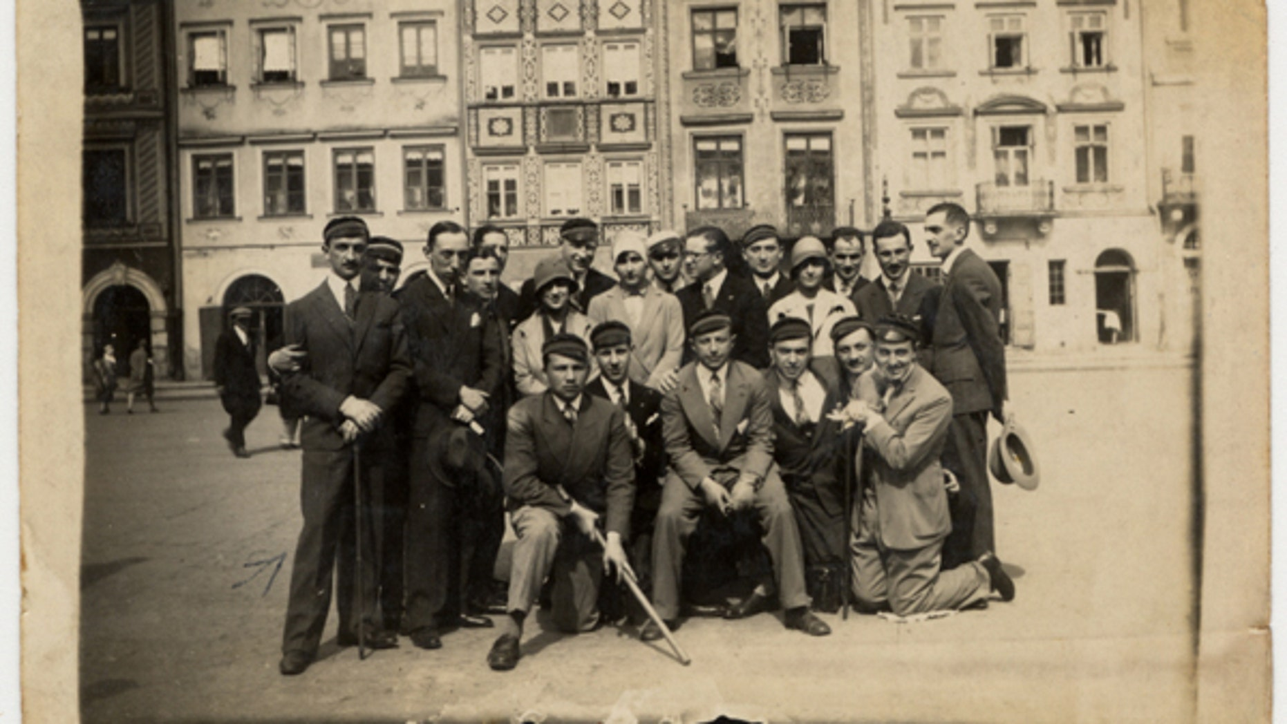 A group of friends, many of whom are wearing university caps, pose for a group portrait on a street in Warsaw. The photo is on display at the United States Holocaust Memorial Museum