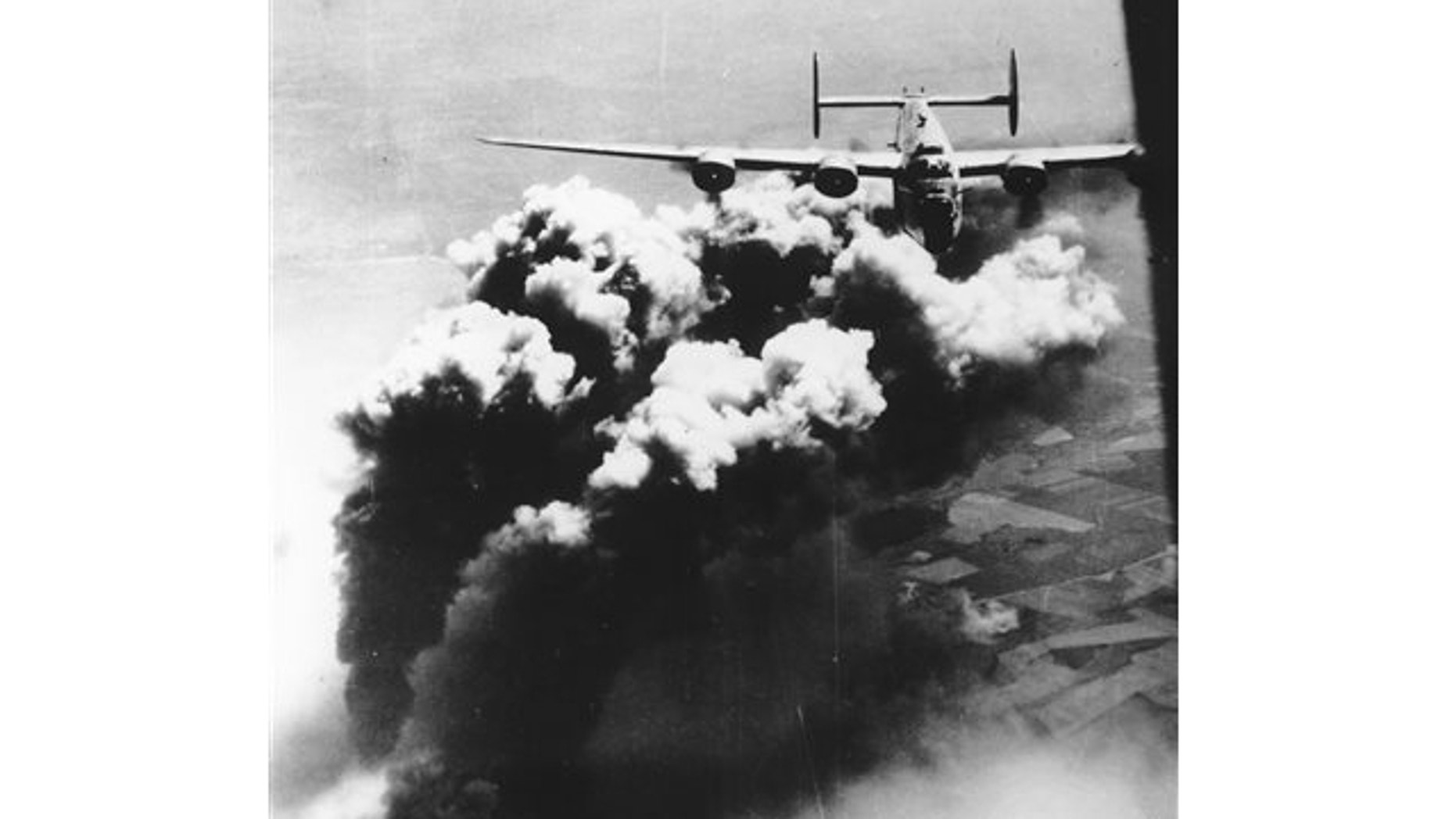 Aug. 1, 1943: A U.S. Army Air Force B-24 Liberator flies with plumes of black smoke rising from bombed facilities of the Astro Romano oil refinery at Ploiesti, Romania.
