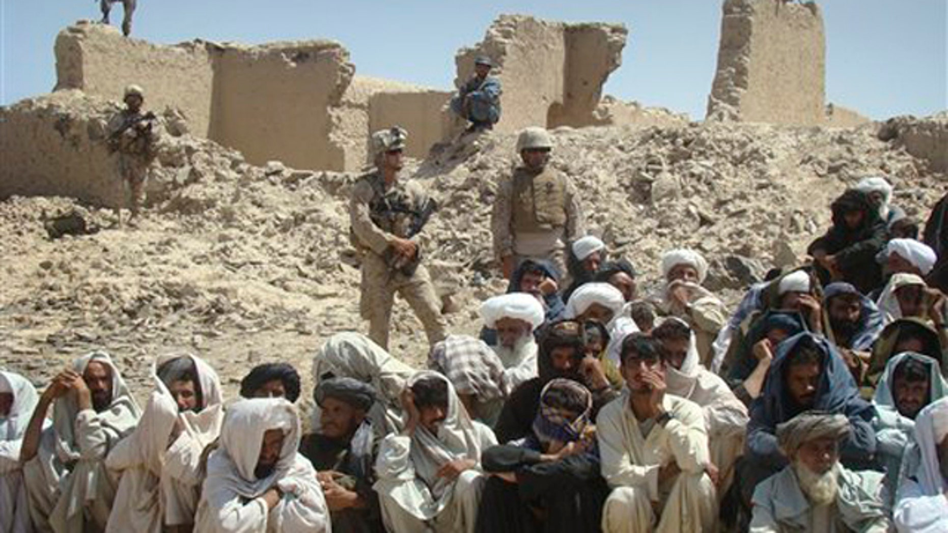In this Aug. 27 photo, Afghan men listen to speeches, as Afghan and U.S. soldiers stand guard, background, in Washer district south of Kabul, Afghanistan.
