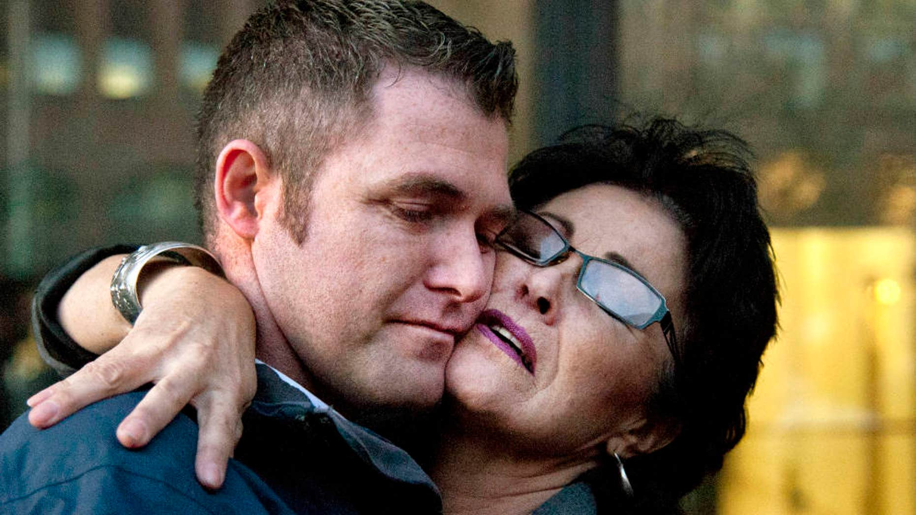 March 3, 2015: Rhonda Firestack-Harvey, right, embraces her son, Roland Gregg outside federal court.