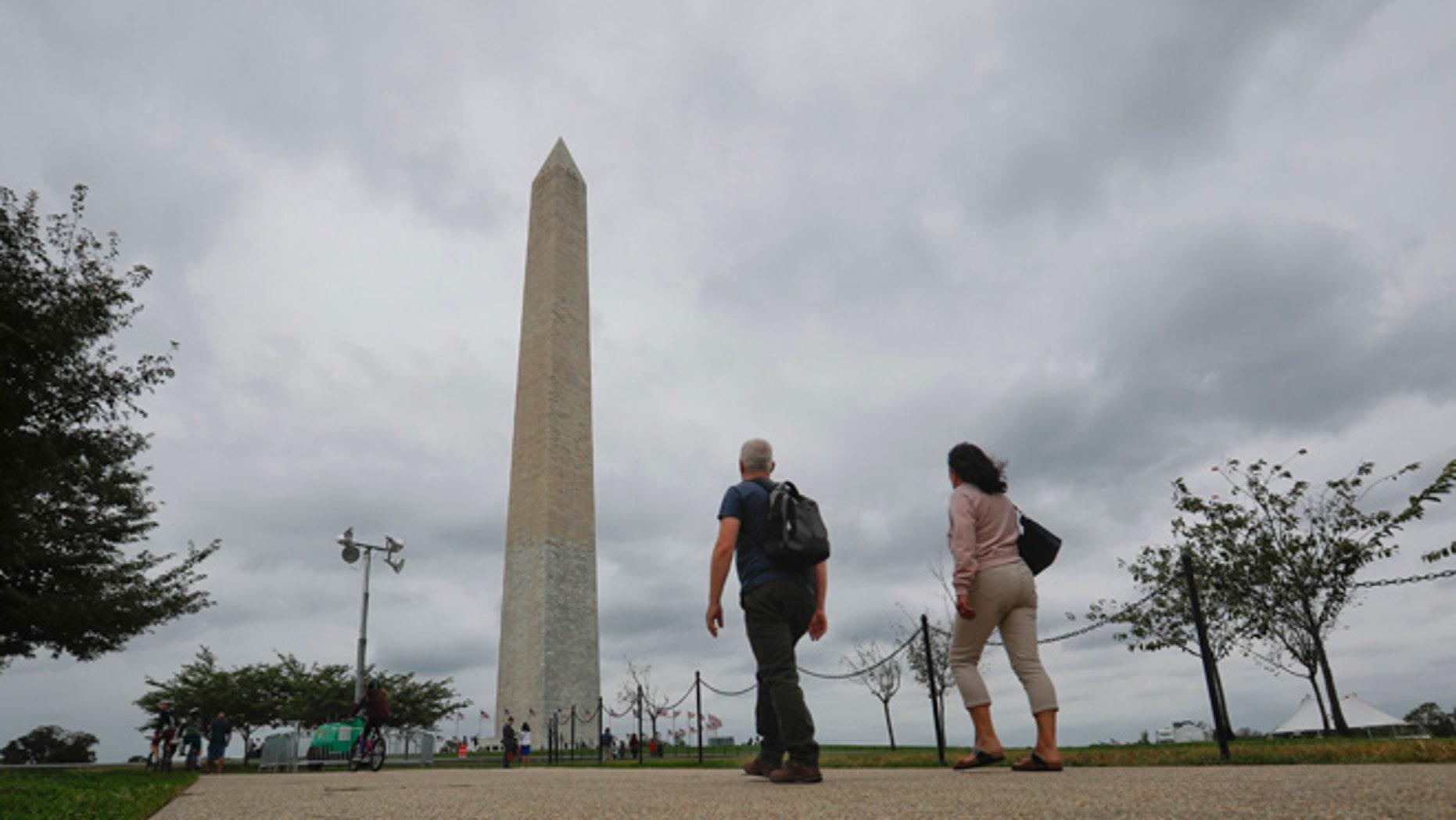 Visitors walks toward the Washington Monument on the National Mall in Washington, Monday, Sept. 26, 2016.