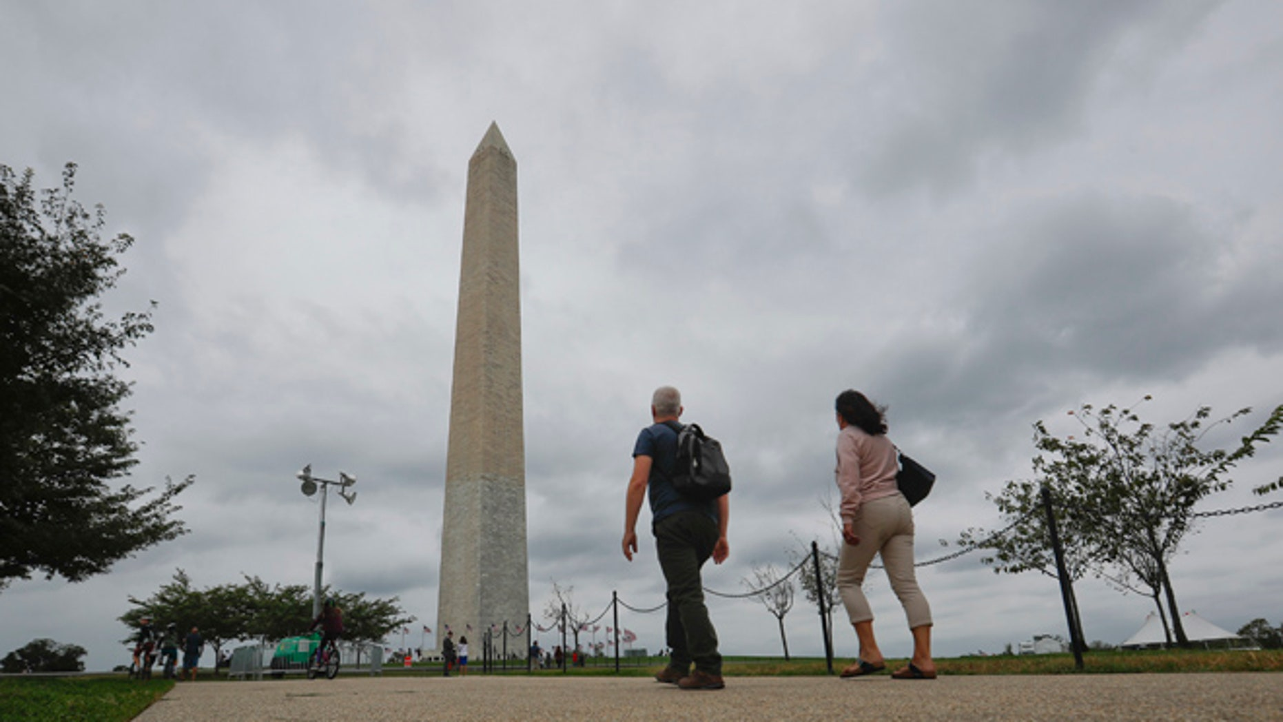 Visitors walks toward the Washington Monument on the National Mall in Washington, Monday, Sept. 26, 2016.