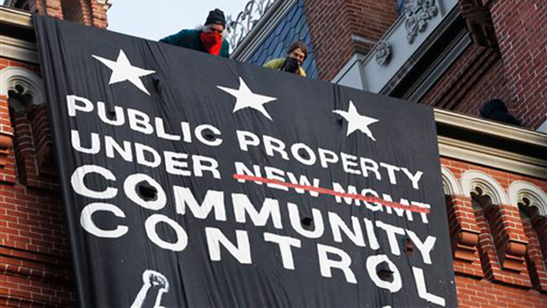 Nov. 19, 2011: A group of protesters inspired by Occupy D.C. protests look out from the roof, after hanging a banner on Franklin School building in Washington, D.C.