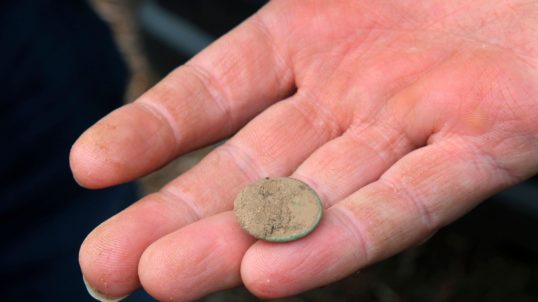 May 5, 2016: Kevin Bradley, project archeologists with Commonwealth Heritage Group, a Michigan-based firm that specializes in archaeological surveying, holds a small button unearthed while looking for artifacts in Chatham, N.J.