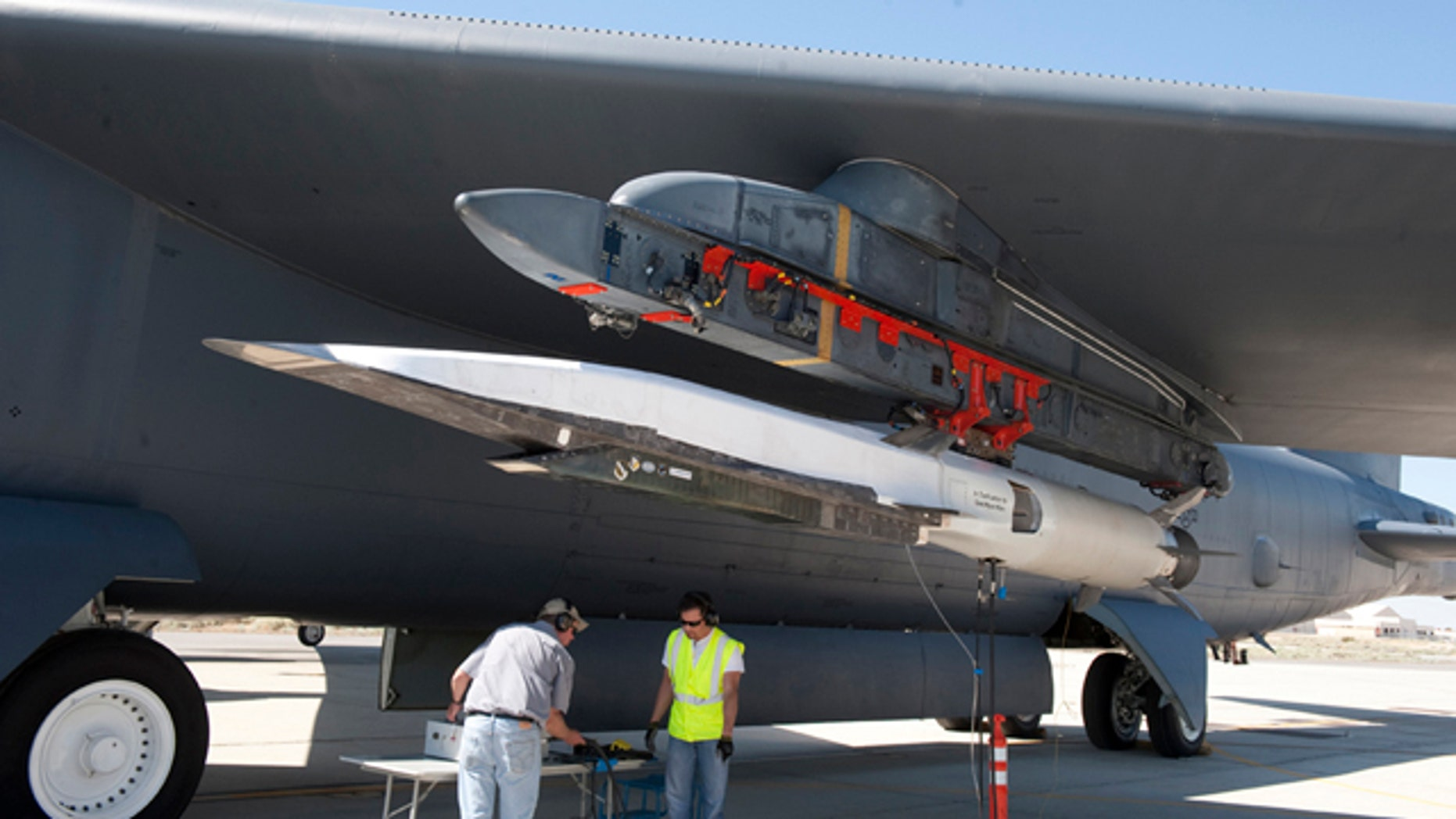 Ground crew members make the final checks to the X-51A Waverider scramjet, which is affixed to an Edwards B-52H Stratofortress, before the Waverider's June 13 flight test.