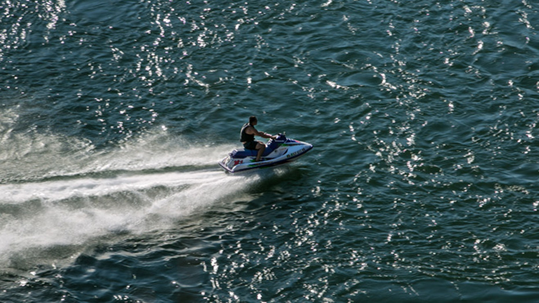 """REDDING, CA - JULY 19:  A man on a jet ski rides up the Sacramento River as viewed on July 19, 2015, in Redding, California. After entering the fourth year of drought, reservoirs continue to flucuate at low levels, Governor Jerry """"Edmund"""" Brown has declared a """"mandatory reduction"""" on water useage for all of California. (Photo by George Rose/Getty Images)"""